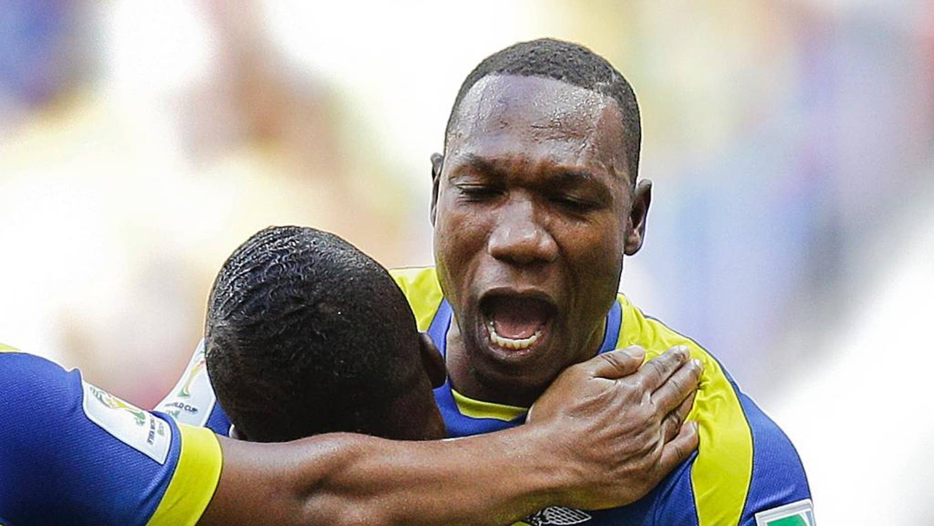 Ecuador's Walter Ayovi celebrates with opening goal scorer Enner Valencia (13) during the group E World Cup soccer match between Switzerland and Ecuador at the Estadio Nacional in Brasilia, Brazil, Sunday, June 15, 2014. (AP Photo/Michael Sohn)