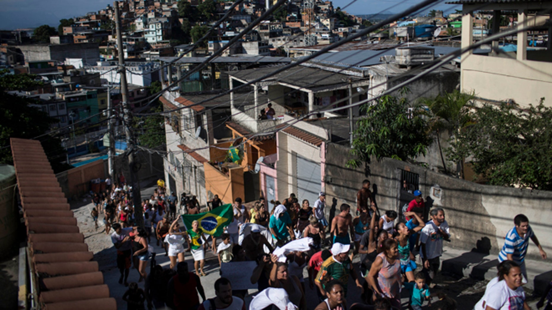 Residents take part in a protest march calling attention to the violence that erupts during police operations against suspected drug traffickers, in the Alemao slum complex in Rio de Janeiro, Brazil, Friday, April 3, 2015. Residents are protesting the shooting deaths of a young boy and a 41-year-old housewife, who were killed by stray bullets in the past few days. (AP Photo/Felipe Dana)