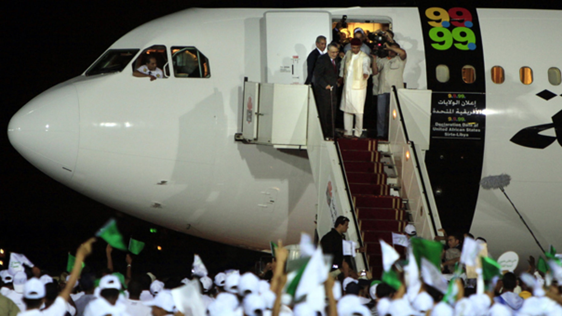 In this Aug. 20, 2009 file photo, hundreds of Libyans an airport in Tripoli welcome Abdel Baset al-Megrahi, who was found guilty of the 1988 Lockerbie bombing, top left.