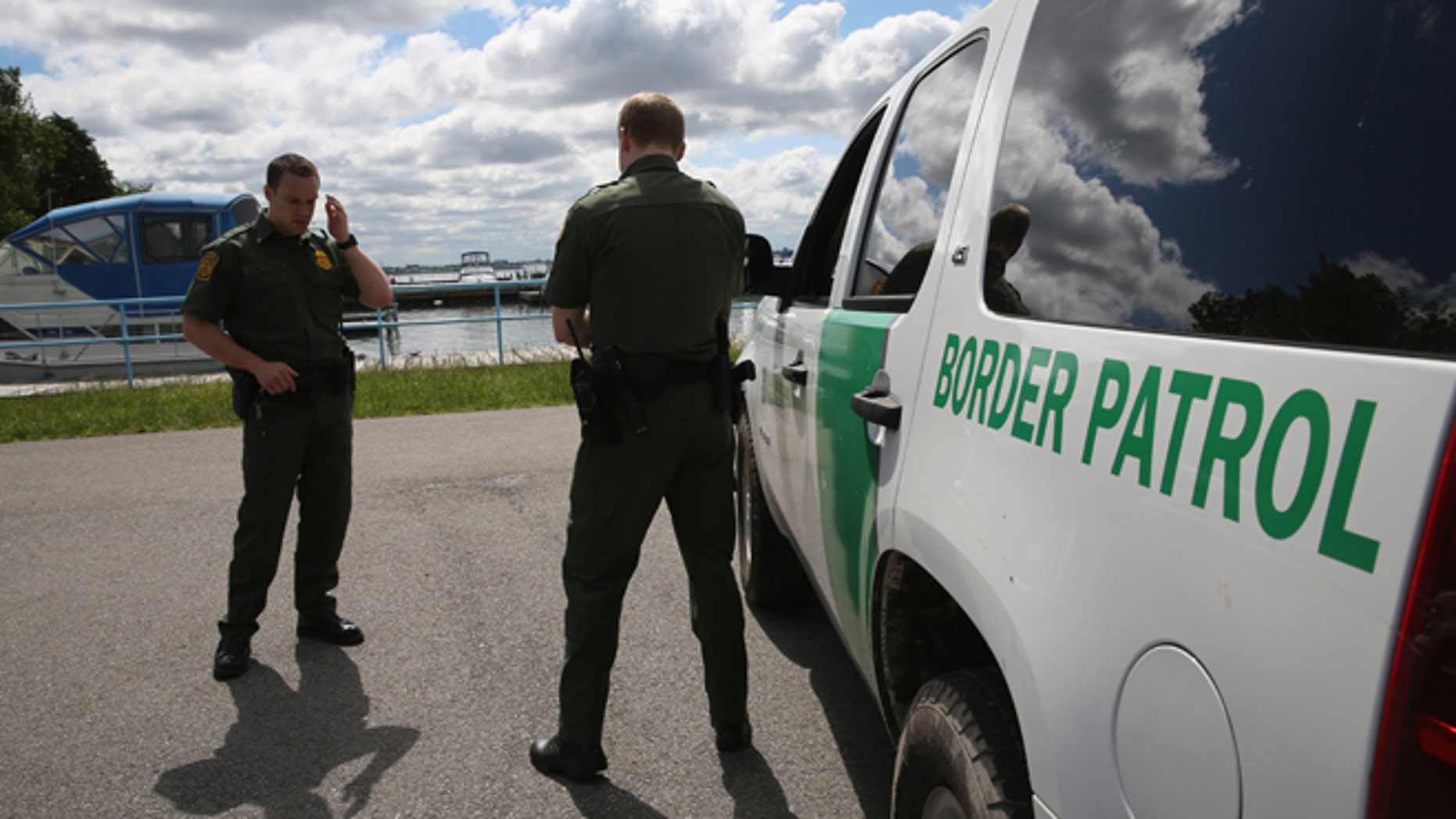 BEAVER ISLAND STATE PARK, NY - JUNE 03: U.S. Border Patrol agents talk while at a marina on the Niagara River at the U.S.-Canada border on June 3, 2013 in Beaver Island State Park, New York. U.S. Customs and Border Protection, which includes the Border Patrol, monitors the 5,525 mile long border, including Alaska, forming the longest international border between two countries in the world.  (Photo by John Moore/Getty Images)