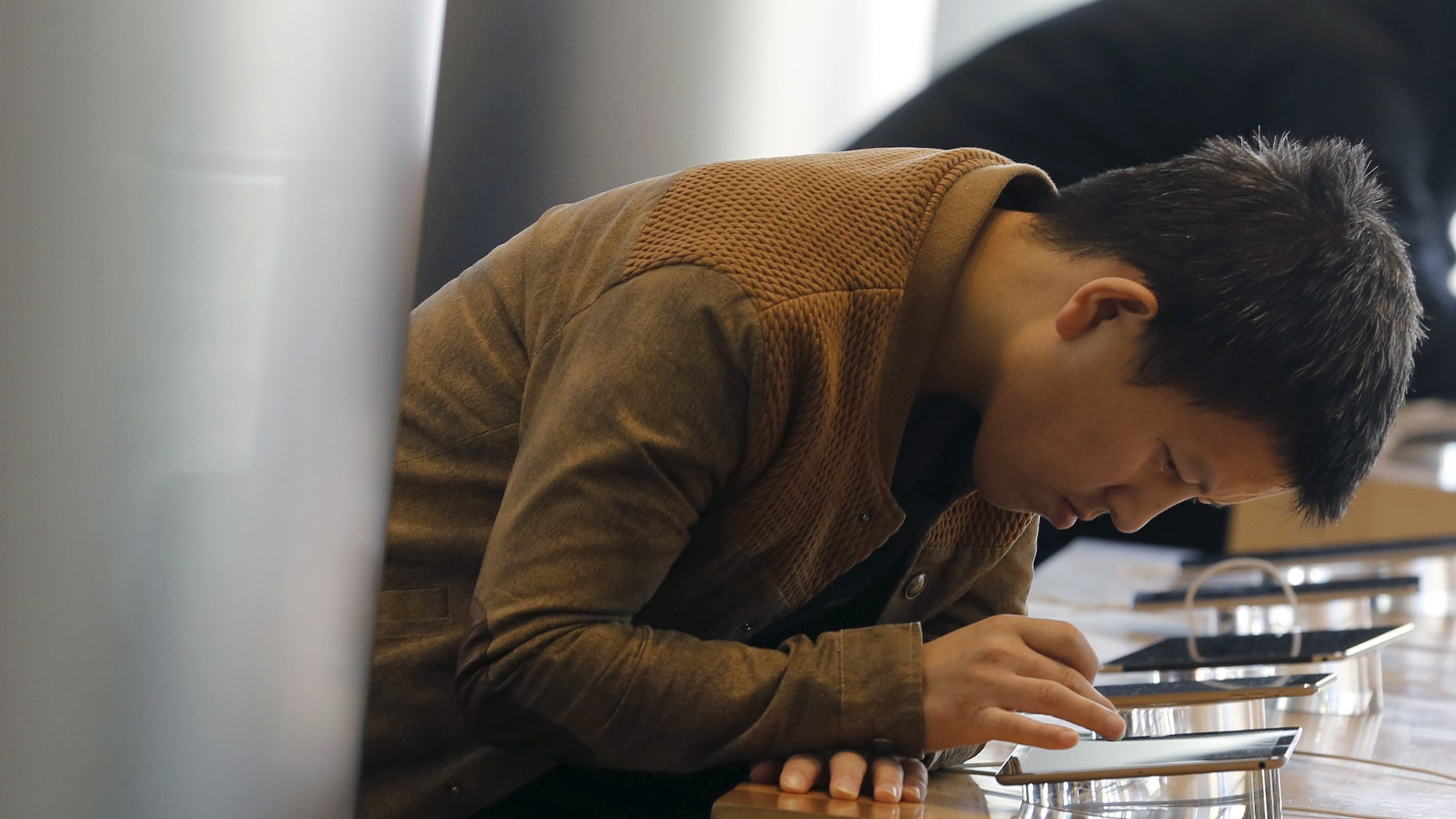 A man tries Apple's iPhone 6 at an Apple store in Beijing, November 2, 2015. (REUTERS/Kim Kyung-Hoon)