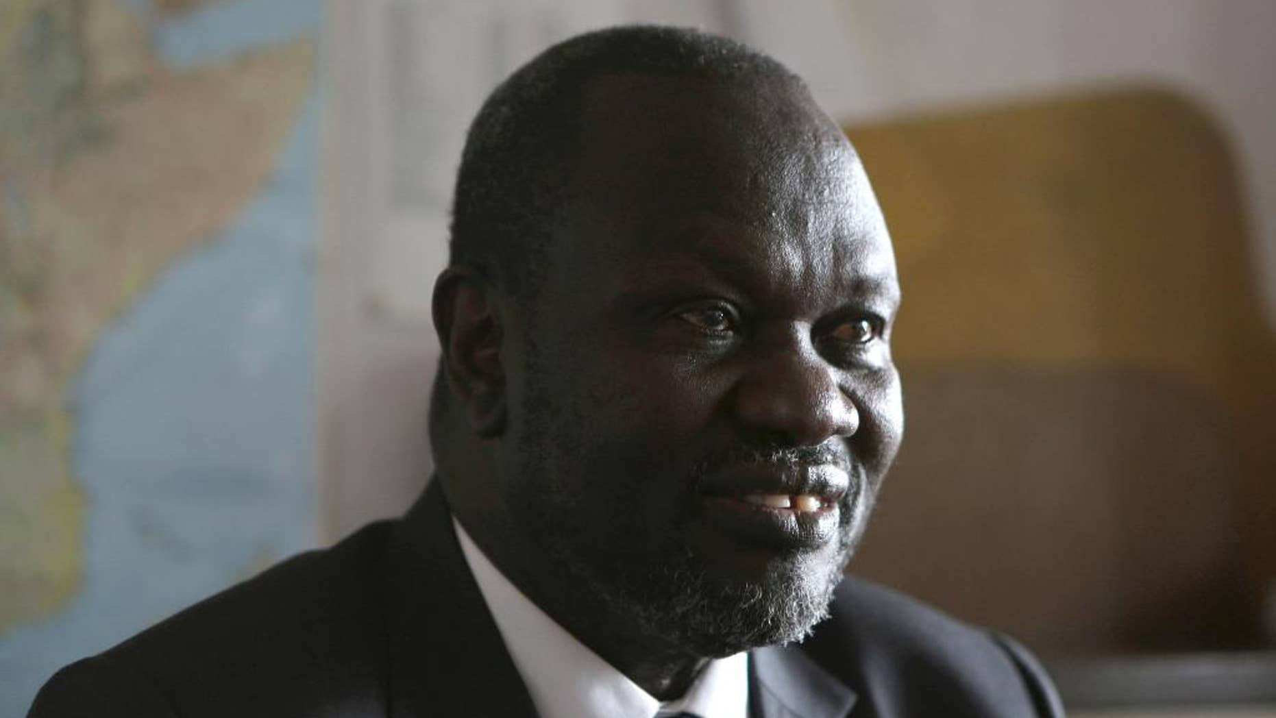 FILE - In this Thursday, Oct. 20, 2016 file photo, South Sudan rebel leader Riek Machar speaks in an interview with The Associated Press in Johannesburg. Riek Machar told The Associated Press in a phone interview on Saturday Dec. 17, 2016, he cannot leave his home in South Africa without first informing South African authorities. (AP Photo/Denis Farrell, File)