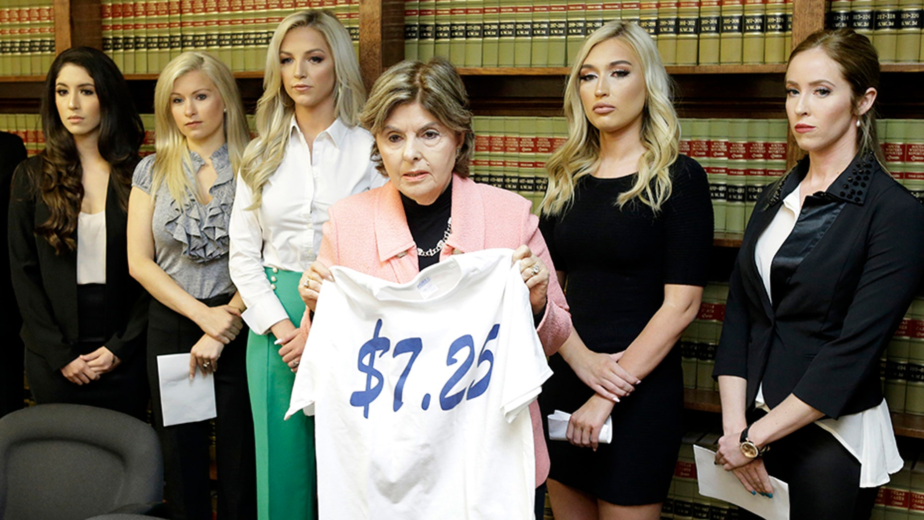 """Attorney Gloria Allred stands among former Houston Texans cheerleaders -- from left, Ashley Rodriguez, Morgan Wiederhold, Kelly Neuner, Hannah Turnbow and Ainsley Parish -- while holding up a shirt printed with """"$7.25,"""" the amount she says the former cheerleaders were paid per hour."""