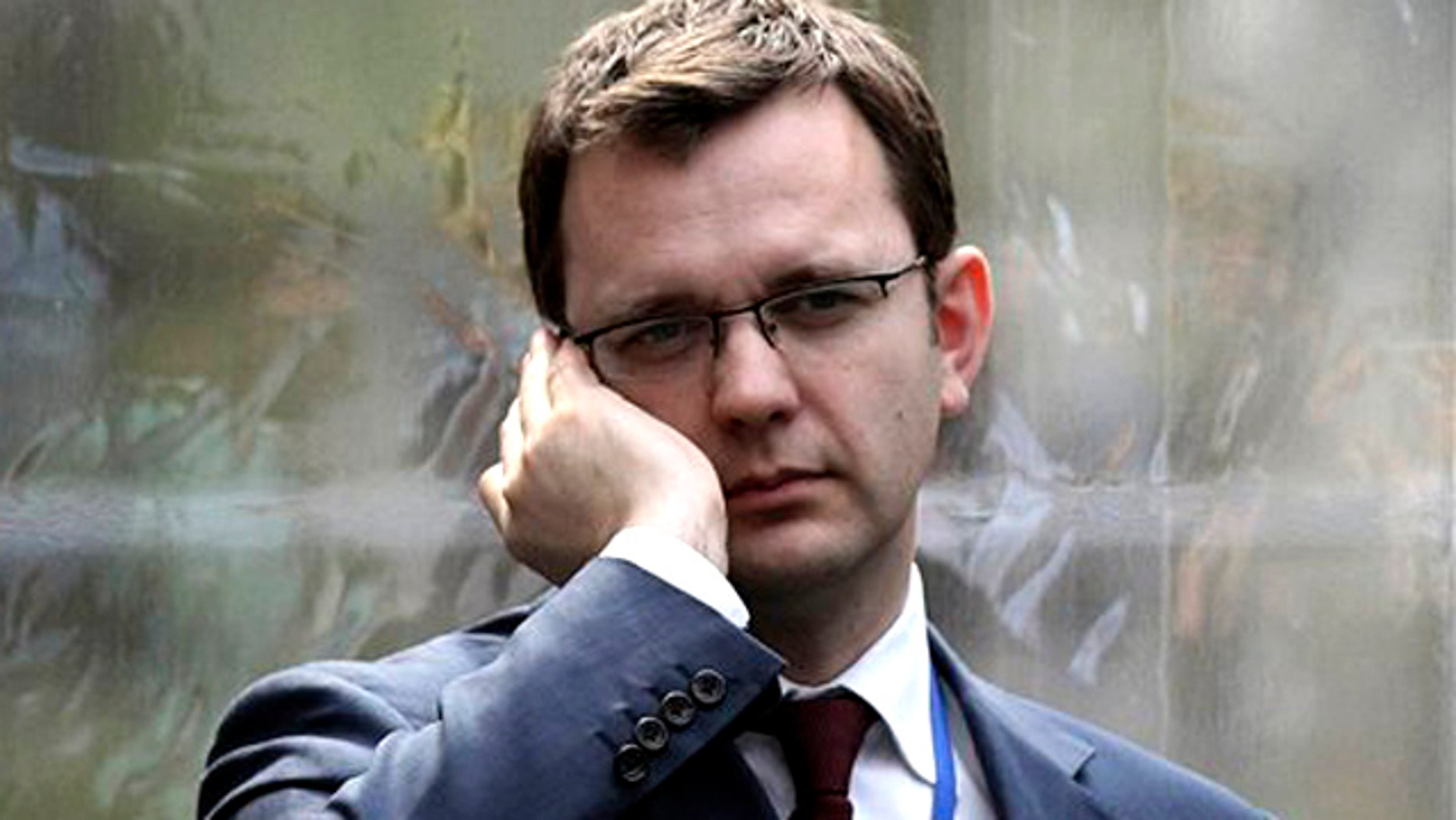 In this April 13, 2010 file photo, Andy Coulson, formerly editor of the tabloid News of the World, and later David Cameron's director of communications, speaks on a mobile phone in London
