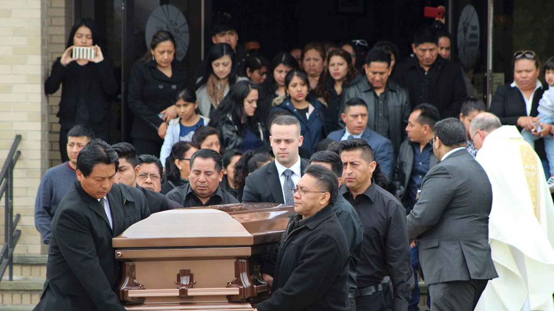 FILE - In this April 19, 2017 file photo, the casket of Justin Llivicura is carried from St. Joseph the Worker Church after Llivicura's funeral in East Patchogue, N.Y. Llivicura, 16, was one of four young men found slain in a suspected MS-13 gang killing in a park in Central Islip, N.Y., on April 12. The gang has been blamed for the deaths of nearly a dozen young people in blue-collar Brentwood and Central Islip since the school year began. (AP Photo/Frank Eltman, File)
