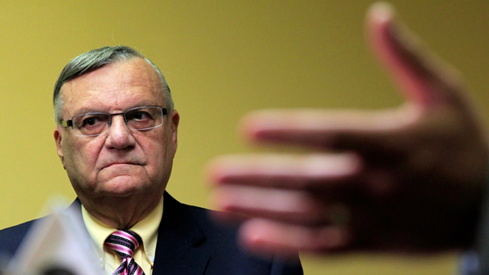 FILE - In this April 3, 2012 file photo, Maricopa County Sheriff Joe Arpaio listens to one of his attorneys during a news conference in Phoenix. Arpaio, who led the way for local police across the country to take up immigration enforcement, is reconsidering his crackdowns _ and other law enforcement officials who followed his lead are expected to eventually back away, too. (AP Photo/Ross D. Franklin, File)