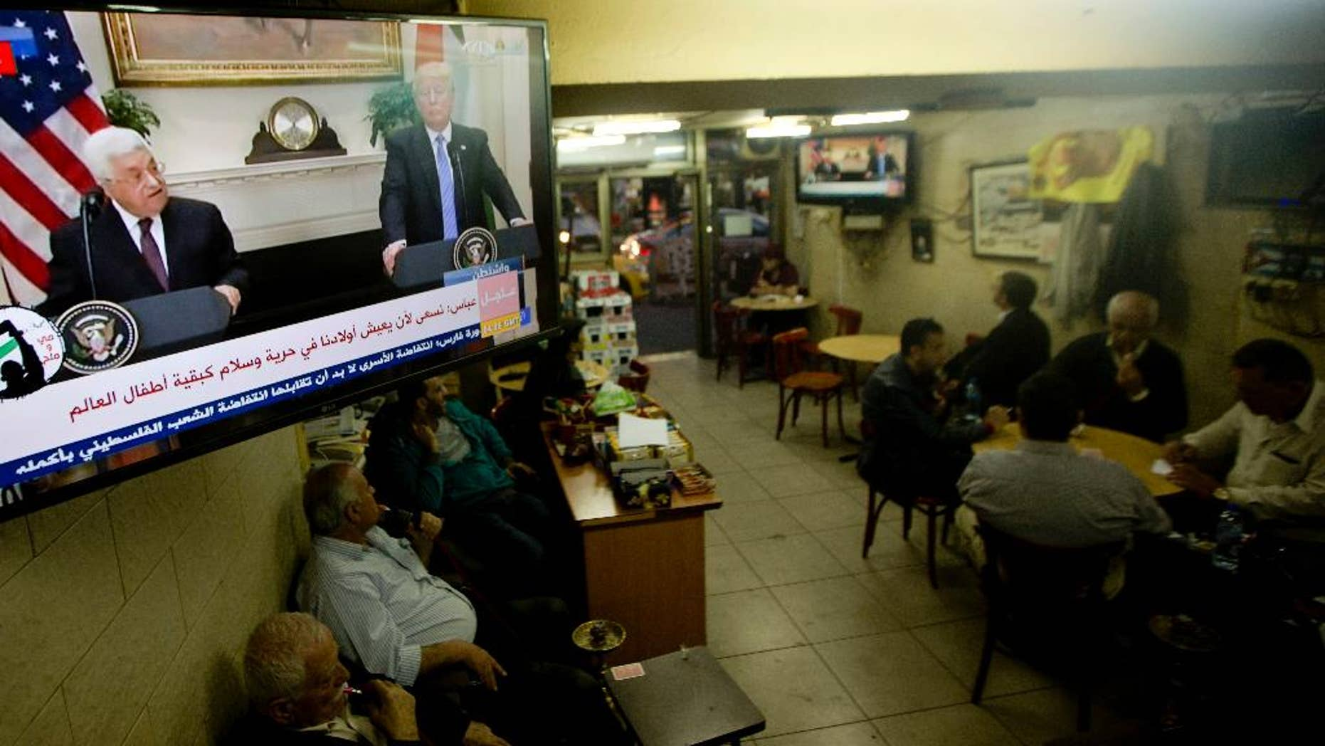"Palestinians play cards at a coffee shop as a television broadcasts a statement in Washington between  President Donald Trump with Palestinian President Mahmoud Abbas, in the West Bank city of Ramallah, Wednesday, May 3, 2017. Trump said Wednesday that the White House is starting a process between the Israelis and Palestinians that ""hopefully will lead to peace."" Abbas said that he's hopeful for bringing about peace with Israel ""based on the vision of two states,"" with the borders of 1967. Israel has rejected the 1967 lines as a possible border, saying it would impose security risks. (AP Photo/Majdi Mohammed)"
