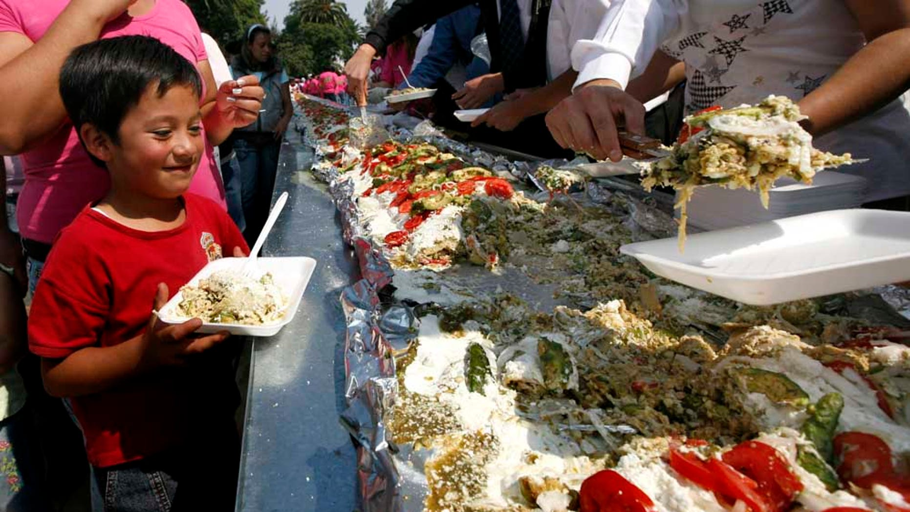 A boy waits to be served a portion of the world's largest 'Enchilada', a traditional Mexican food, during the National Enchilada Fair at the neighborhood of Iztapalapa in Mexico City, Sunday, Oct. 17, 2010. The enchilada, measuring 70 meters long and 1,416 kgs, entered the famous Guinness Record book Sunday. (AP Photo/Marco Ugarte)