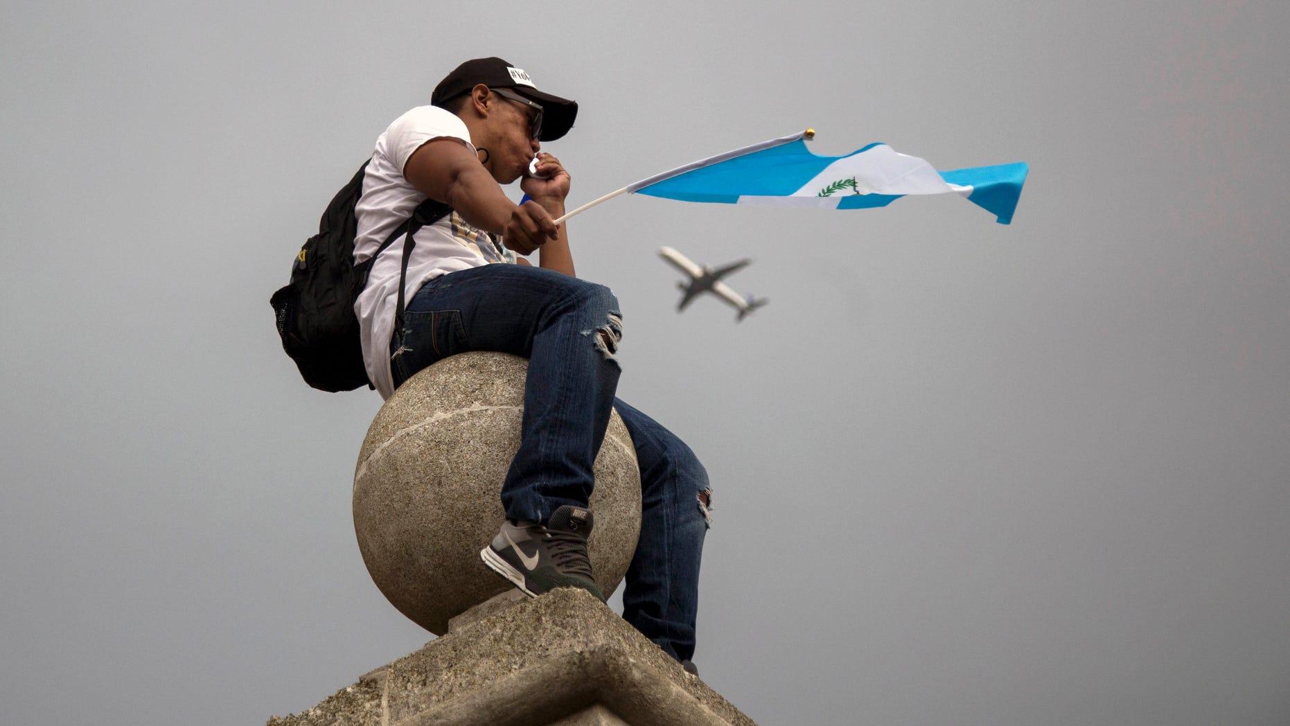 """En esta imagen, tomada el 27 de agosto de 2015, un manifestante ondea una bandera de Guatemala sentado en lo alto de una columna en la catedral Metropolitana durante una huelga nacional para exigir la renuncia del presidente del país, Otto Pérez Molina, en la ciudad de Guatemala. La presión sobre el mandatario va en aumento, con negocios y oficinas gubernamentales cerradas y multitudinarias protestas, mientras el fiscal general del Estado le instó a dimitir """"para evitar una ingobernabilidad que podría desestabilizar la nación"""". (Foto AP/Luis Soto)"""