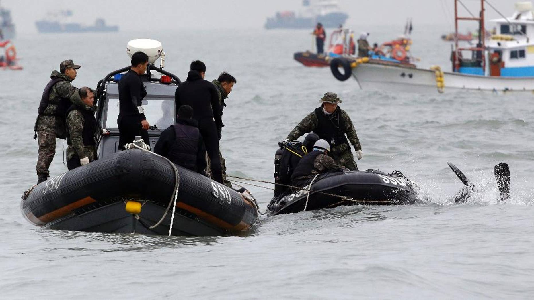 South Korean navy's frogman dives into a water to search passengers believed to have been trapped in the sunken ferry Sewol in the water off the southern coast near Jindo, south of Seoul, South Korea, Saturday, April 19, 2014. The captain of the sunken South Korean ferry was arrested Saturday on suspicion of negligence and abandoning people in need, as investigators looked into whether his evacuation order came too late to save lives. Two crew members were also arrested, a prosecutor said. (AP Photo/Lee Jin-man)