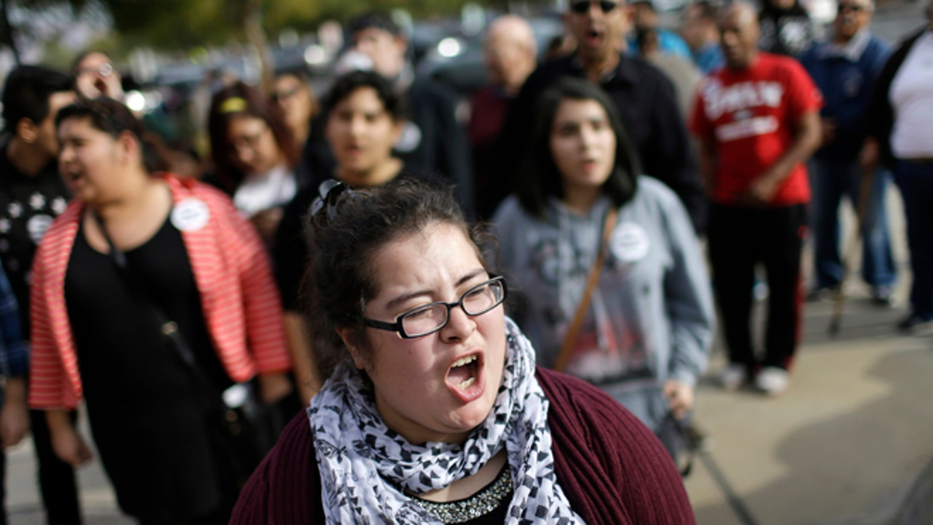 Dulce Valencia and others chant during a protest Wednesday, Jan. 28, 2015, in Las Vegas. A group was demanding that Nevada Attorney General Adam Laxalt drop a lawsuit against President Barack Obama's immigration action. (AP Photo/John Locher)