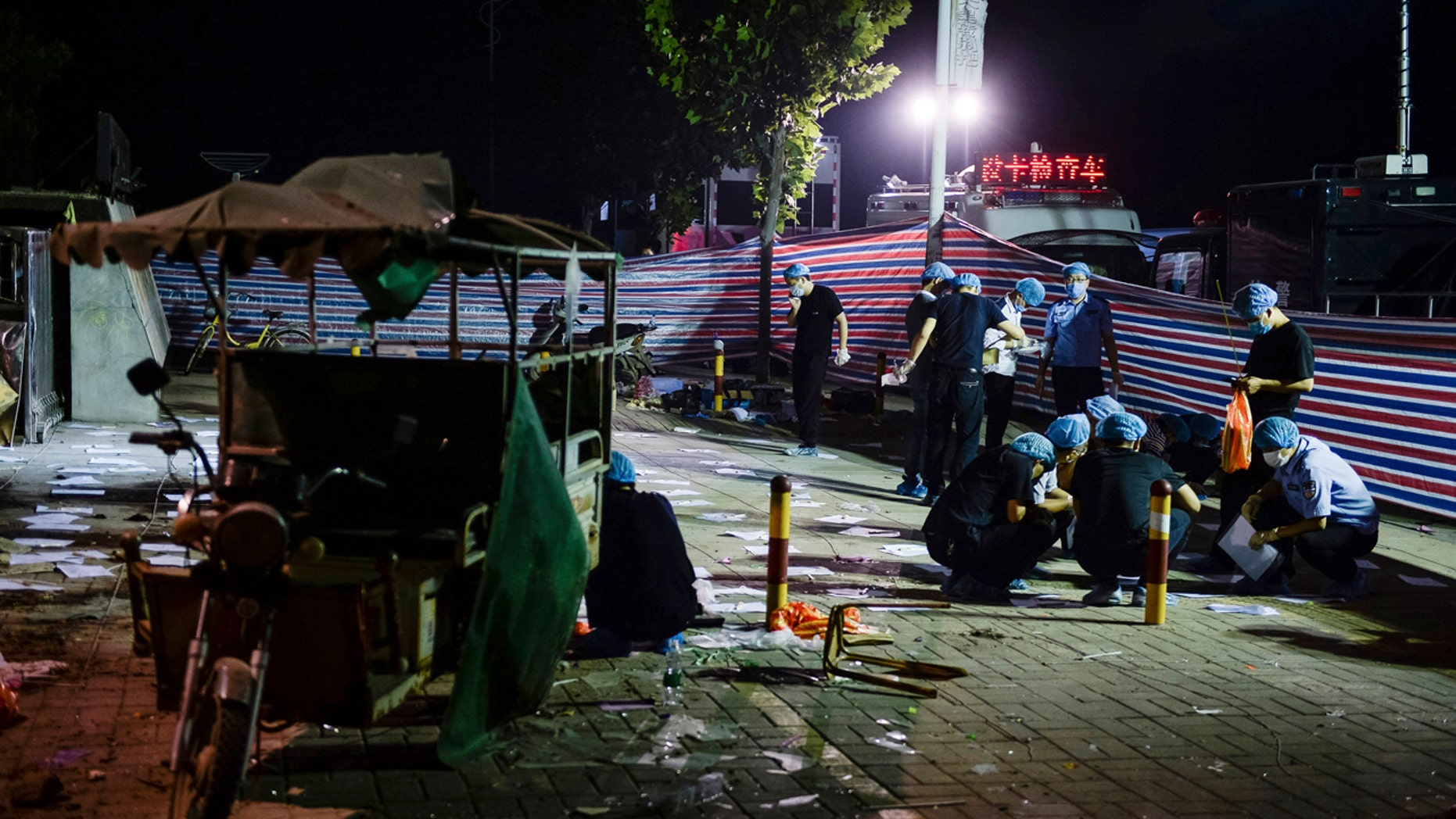 In this photo released by China's Xinhua News Agency, investigators work early Friday, June 16, 2017, at the scene of an explosion outside a kindergarten in Fengxian County in eastern China's Jiangsu Province.
