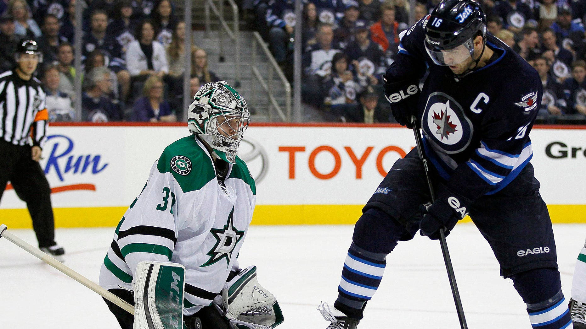 Winnipeg Jets' Andrew Ladd's (16) deflection is stopped by Dallas Stars' goaltender Kari Lehtonen (32) during second-period NHL hockey game action in Winnipeg, Manitoba, Friday, Oct. 11, 2013. (AP Photo/The Canadian Press, John Woods)