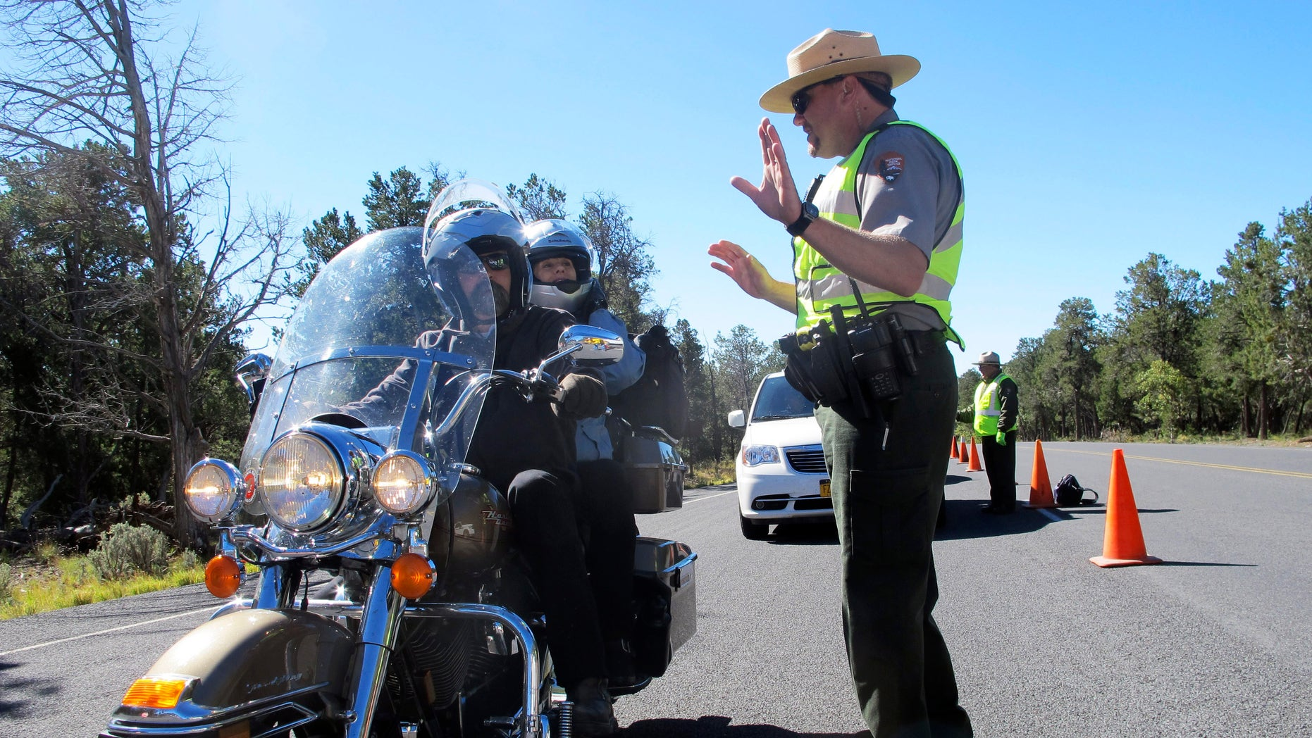 Grand Canyon National Park Ranger Jason Morris talks to people on a motorcycle at the closed park entrance on Thursday, Oct. 3, 2013 in Ariz.  More than 400 national parks are closed as Congress remains deadlocked over federal government funding.  (AP Photo/Brian Skoloff)