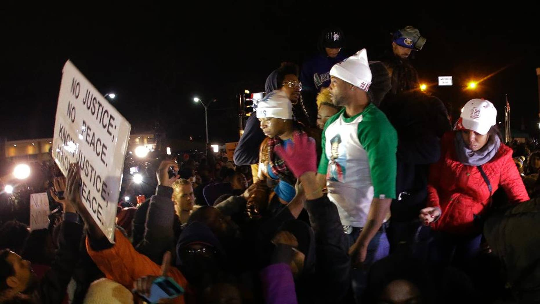 FILE - In this Nov. 24, 2014 file photo Louis Head, center right, Michael Brown's stepfather, and Brown's mother Lesley McSpadden, center left, react as  they listen to the announcement that a grand jury decided not to indict Ferguson police officer Darren Wilson who fatally shot 18-year-old  Brown. Brown has apologized for angry comments he made after the decision was announced, but said his remarks had nothing to do with the arson and looting that ravaged Ferguson and the surrounding area. (AP Photo/Charlie Riedel, File)
