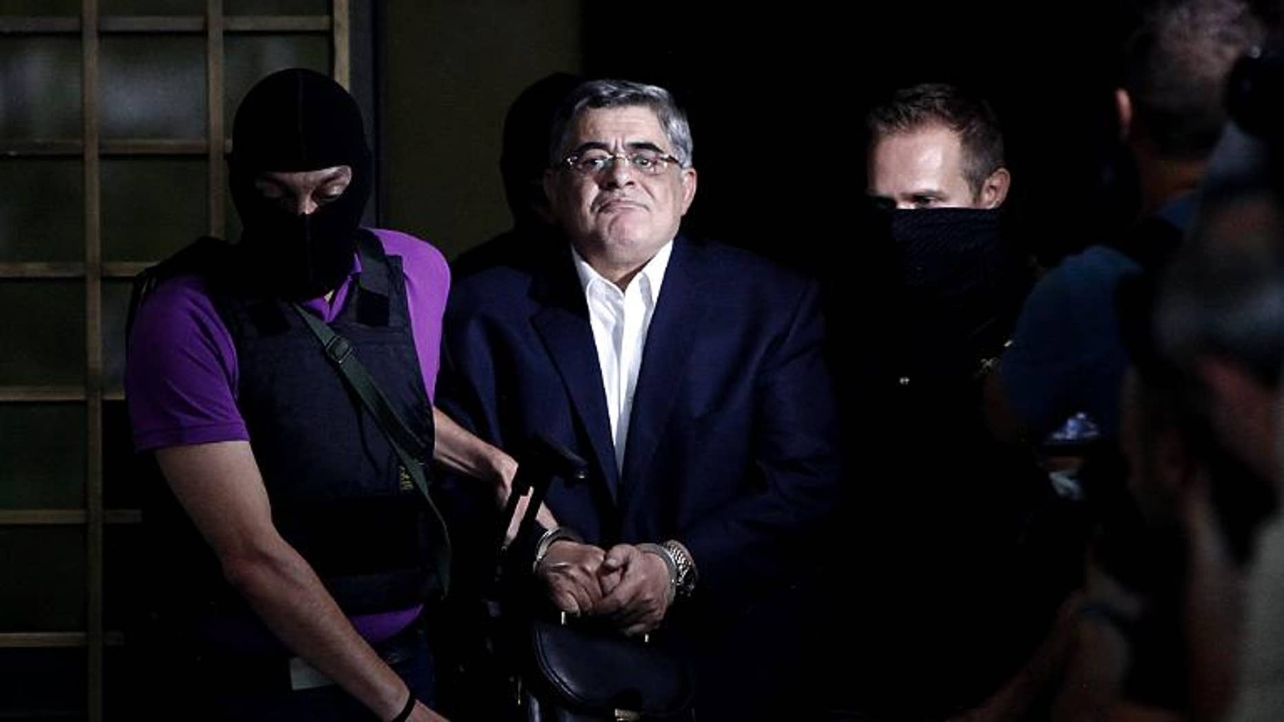The leader of Greece's Golden Dawn party Nikos Michaloliakos is escorted by masked police officers in Athens, on September 28, 2013
