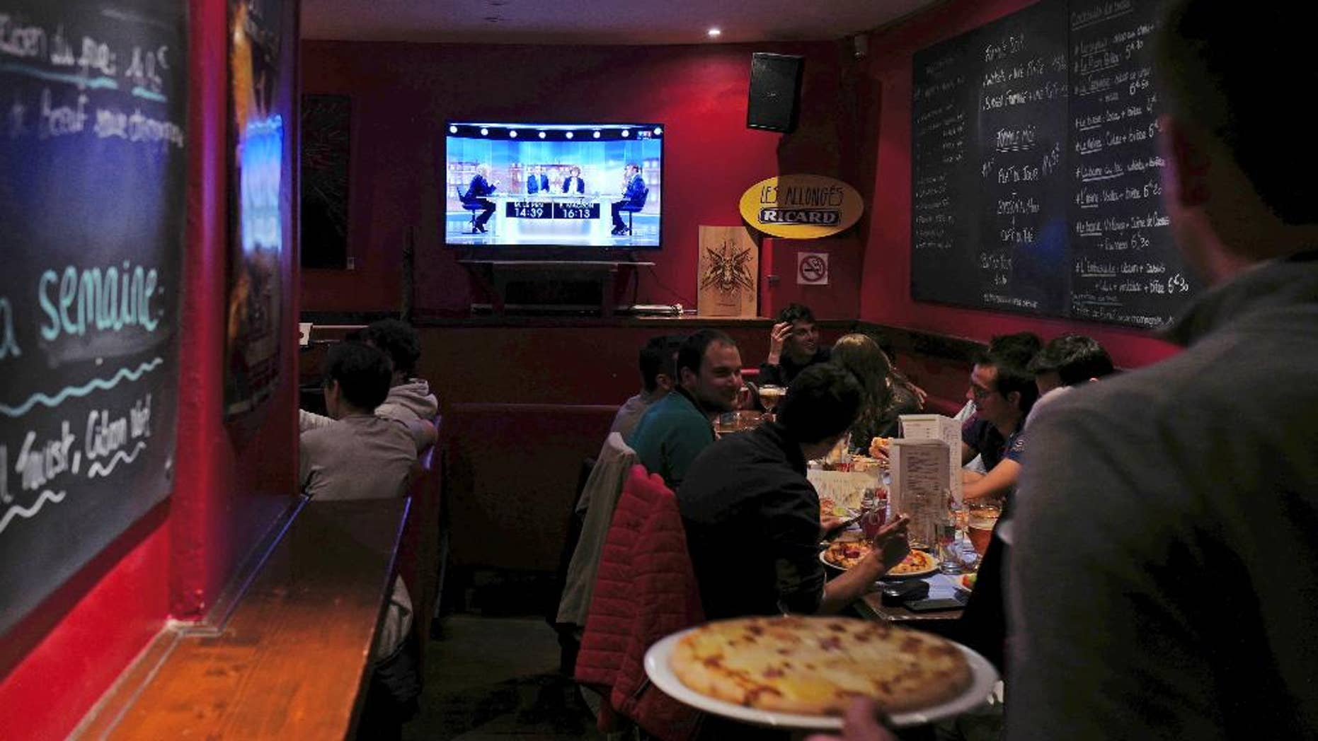 People watch a live broadcast television debate with French centrist presidential candidate Emmanuel Macron, right, and far-right candidate Marine Le Pen, in a restaurant in Lille, northern France, Wednesday, May 3, 2017.  Le Pen and Emmanuel Macron exchanged barbs and insults on Wednesday during their sole televised debate ahead of Sunday's runoff election. (AP Photo/Michel Spingler)