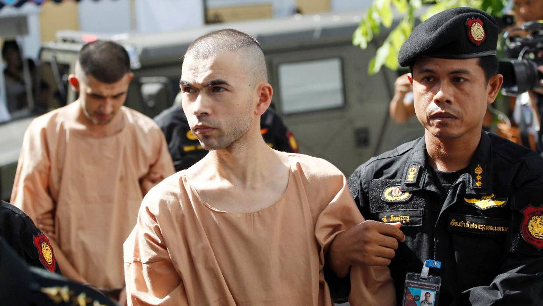 FILE - In this Nov. 24, 2015 file photo, police officers escort suspects in the Aug. 17 blast at Erawan Shrine, Bilal Mohammad, front, and Mieraili Yusufu, rear, as they arrive at a military court in Bangkok, Thailand. Testimony begun Tuesday, Nov. 15, 2016 in the trial of two men accused of the deadly 2015 bombing at a Bangkok landmark after a dispute over the defendants' translators. (AP Photo/Sakchai Lalit, File)
