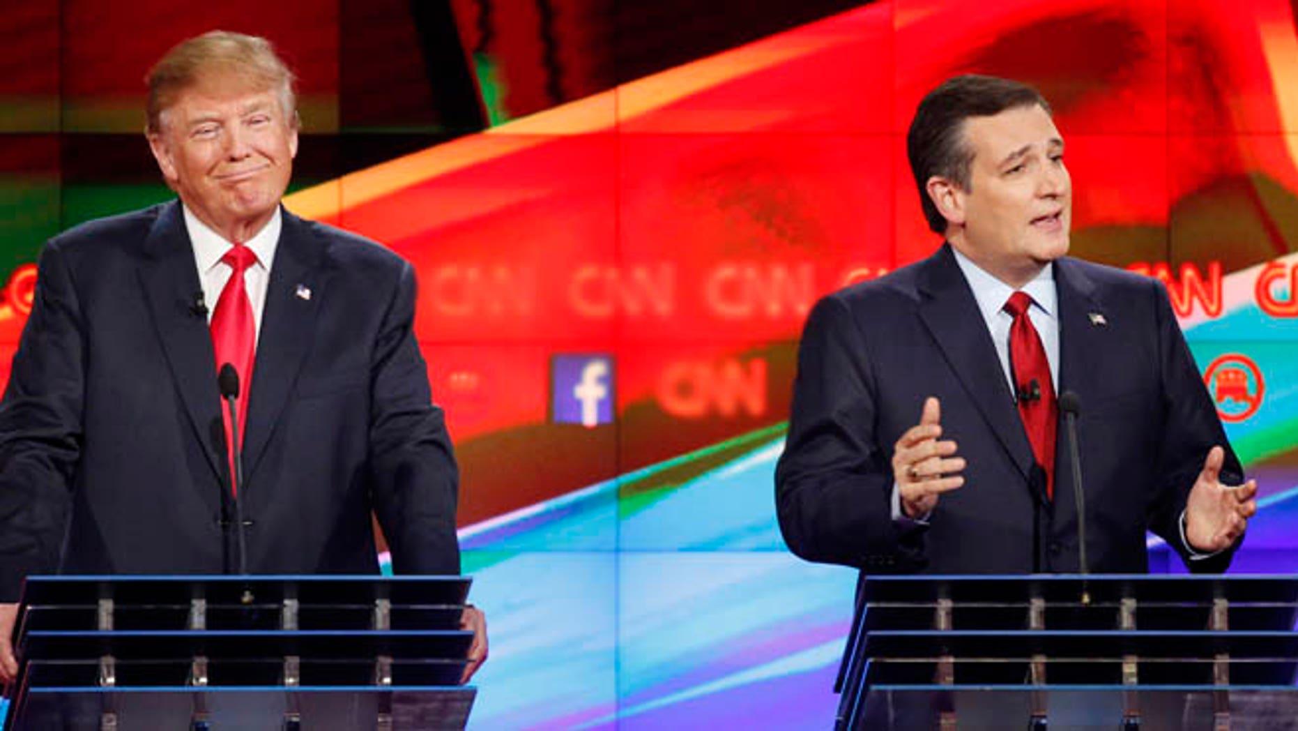 Ted Cruz, right, makes a point as Donald Trump reacts during the CNN Republican presidential debate at the Venetian Hotel & Casino on Tuesday, Dec. 15, 2015, in Las Vegas. (AP Photo/John Locher)