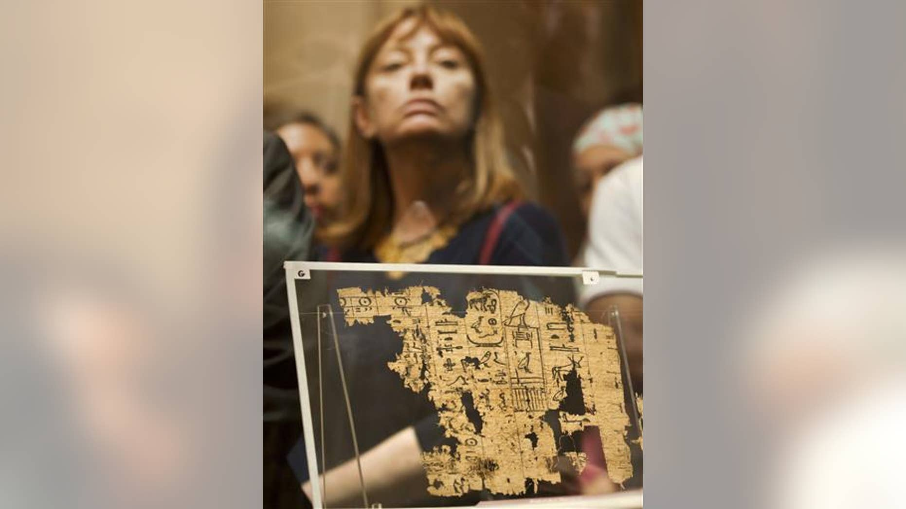 A visitor looks at one of the oldest papyri in the history of Egyptian writing among the collection of King Khufu papyri discovered at Wadi El-Jarf port, as it is on display for the first time at the Egyptian museum in Cairo, Egypt, Thursday, July 14, 2016.