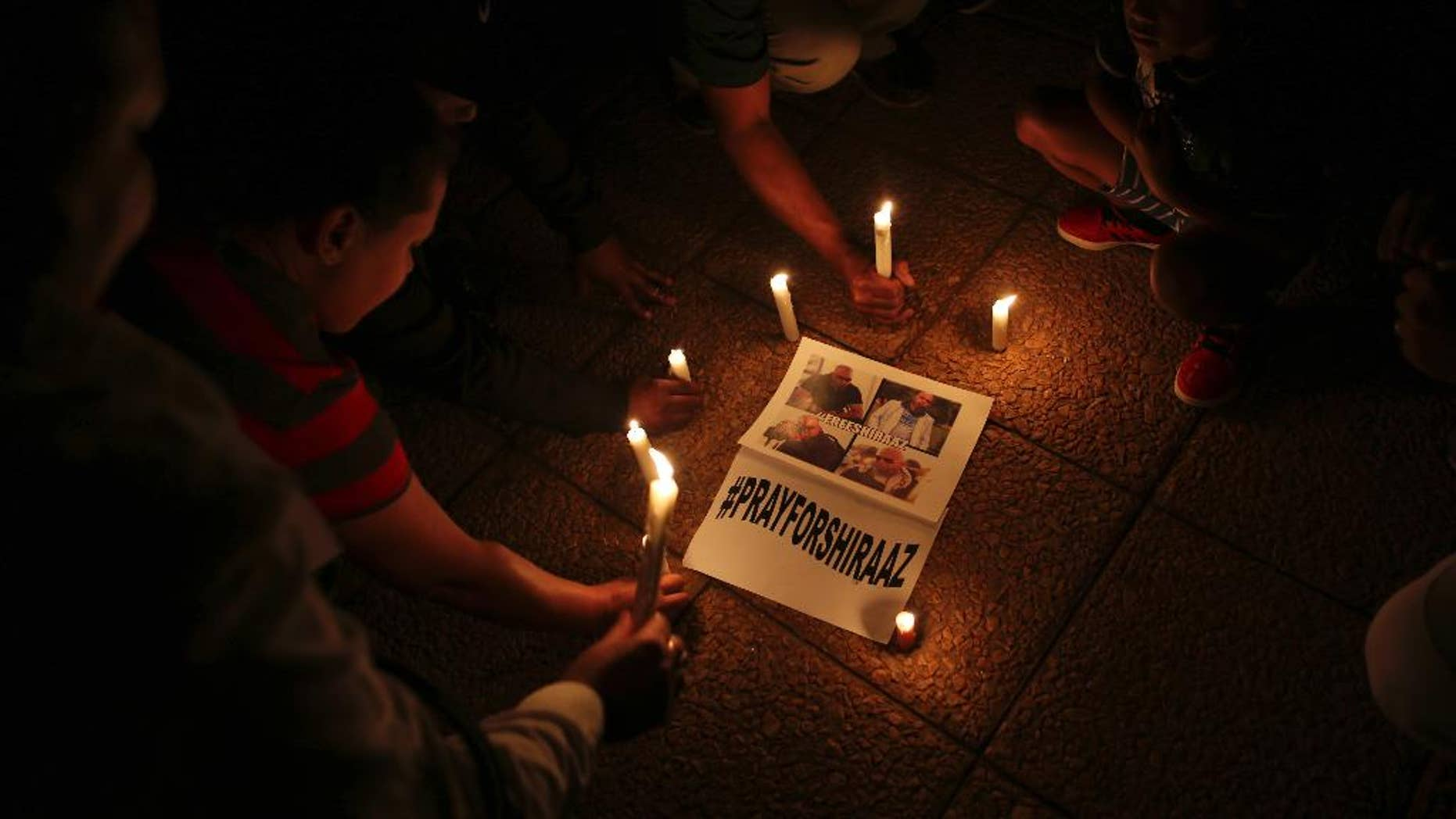 South Africans light candles during a vigil held in Johannesburg Wednesday, Jan. 18, 2017, for South African freelance photographer Shiraaz Mohamed who was abducted in Syria last week. People prayed and held signs calling for the safe return of Mohamed who was kidnapped on Jan. 10, while traveling with aid workers to Syria's border with Turkey. (AP Photo/Denis Farrell)