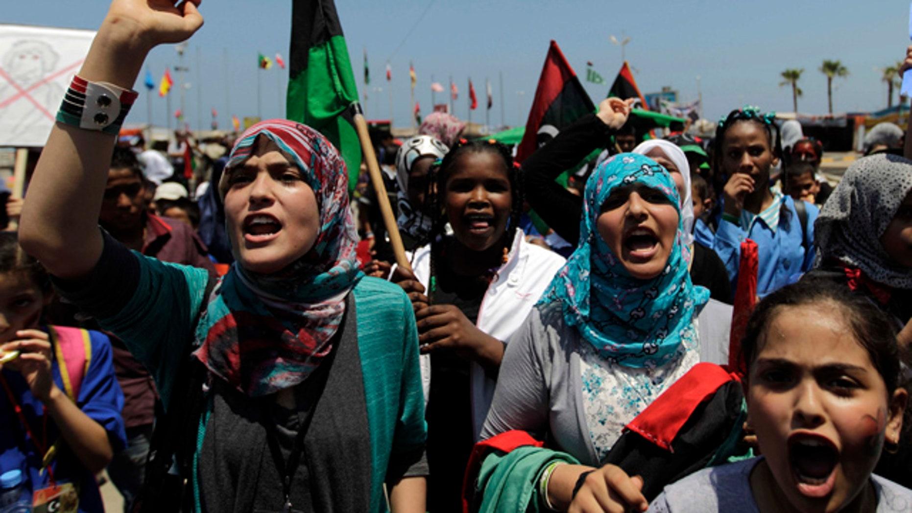 June 25: School students chant slogans against Muammar al-Qaddafi during a demonstration at the court square in the rebel-held capital Benghazi, Libya.