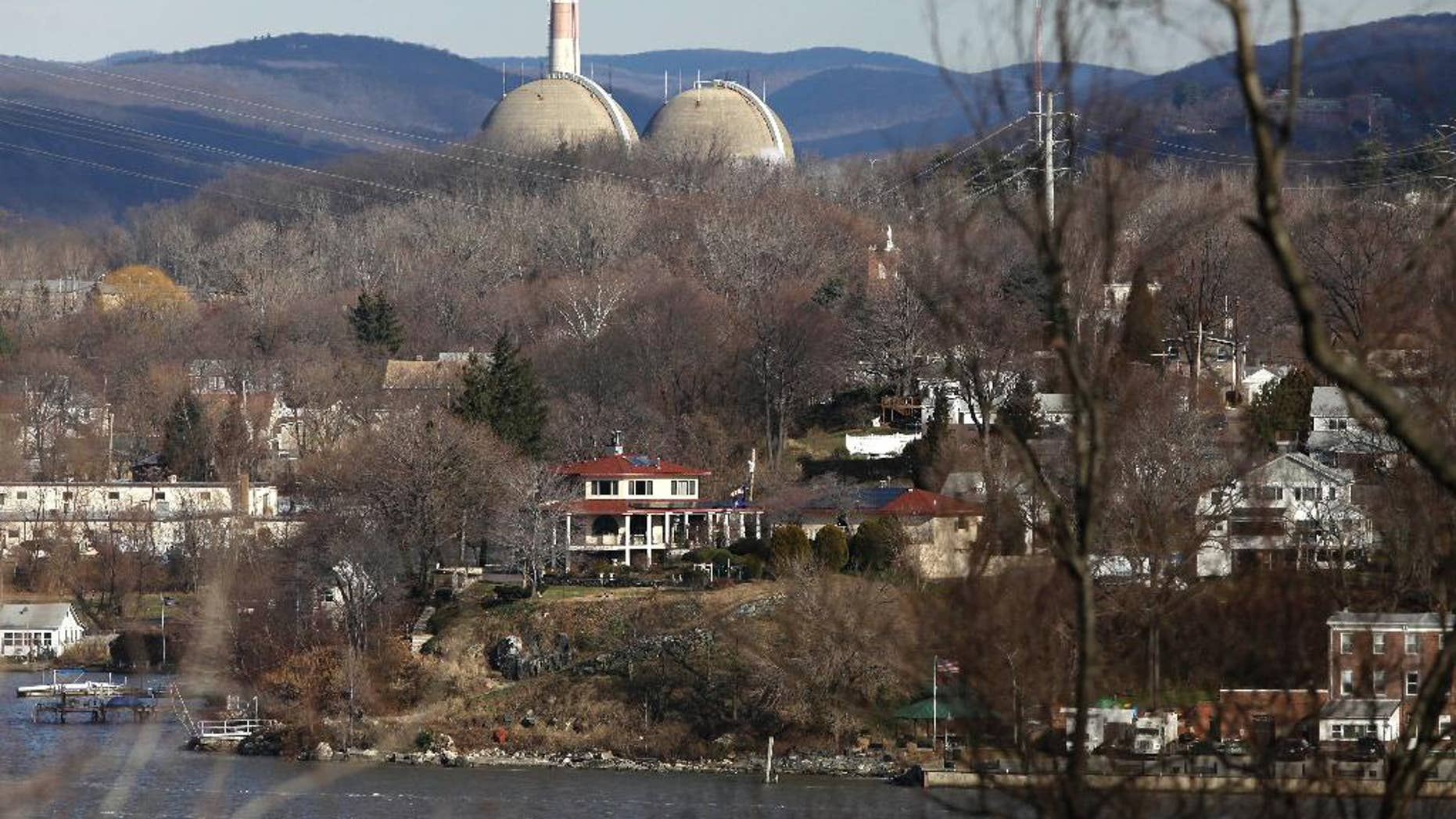 FILE - In this Wednesday, Dec. 16, 2009 photo, reactor containment domes of the Indian Point nuclear power plant in Buchanan, N.Y. rise above homes just north of the town of Verplanck, N.Y. as seen from the Stony Point Historic Site. The aging facility just north of New York City will close by April 2021 under a deal with Gov. Andrew Cuomo, who has long argued it should be shuttered to protect the millions of people living nearby. (AP Photo/Julie Jacobson)