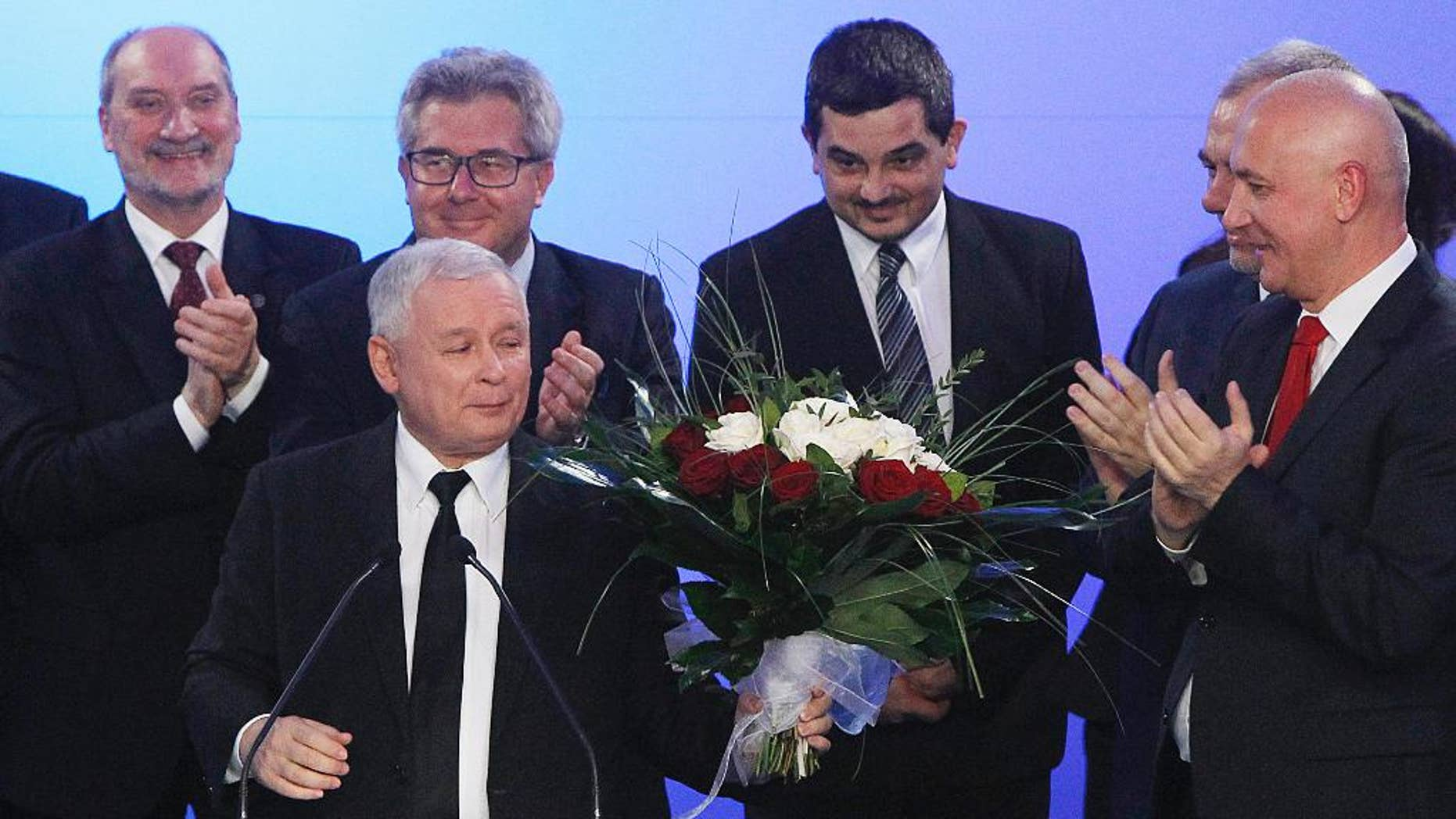 The Law and Justice party leader Jaroslaw Kaczynski receives flowers during the election night after exit polls were announced following the end of the first round of the local elections, in Warsaw, Poland, Sunday, Nov. 26, 2006. The elections exemplify the ongoing political struggle in Poland between the ruling Civic Platform party and opposition Law and Justice, in Warsaw, Poland, Sunday, Nov. 16, 2014.(AP Photo/Czarek Sokolowski)