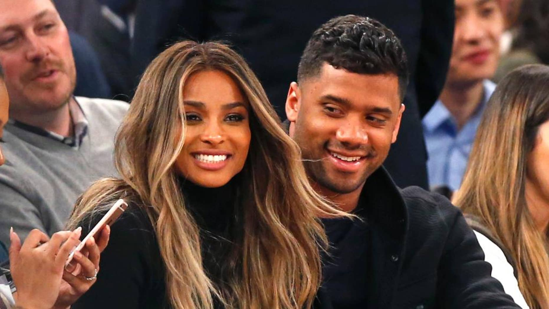 In this Feb. 9, 2016 file photo, singer Ciara, second from left, and Seattle Seahawks quarterback Russell Wilson sit courtside while attending an NBA basketball game between the New York Knicks and the Washington Wizards in New York.