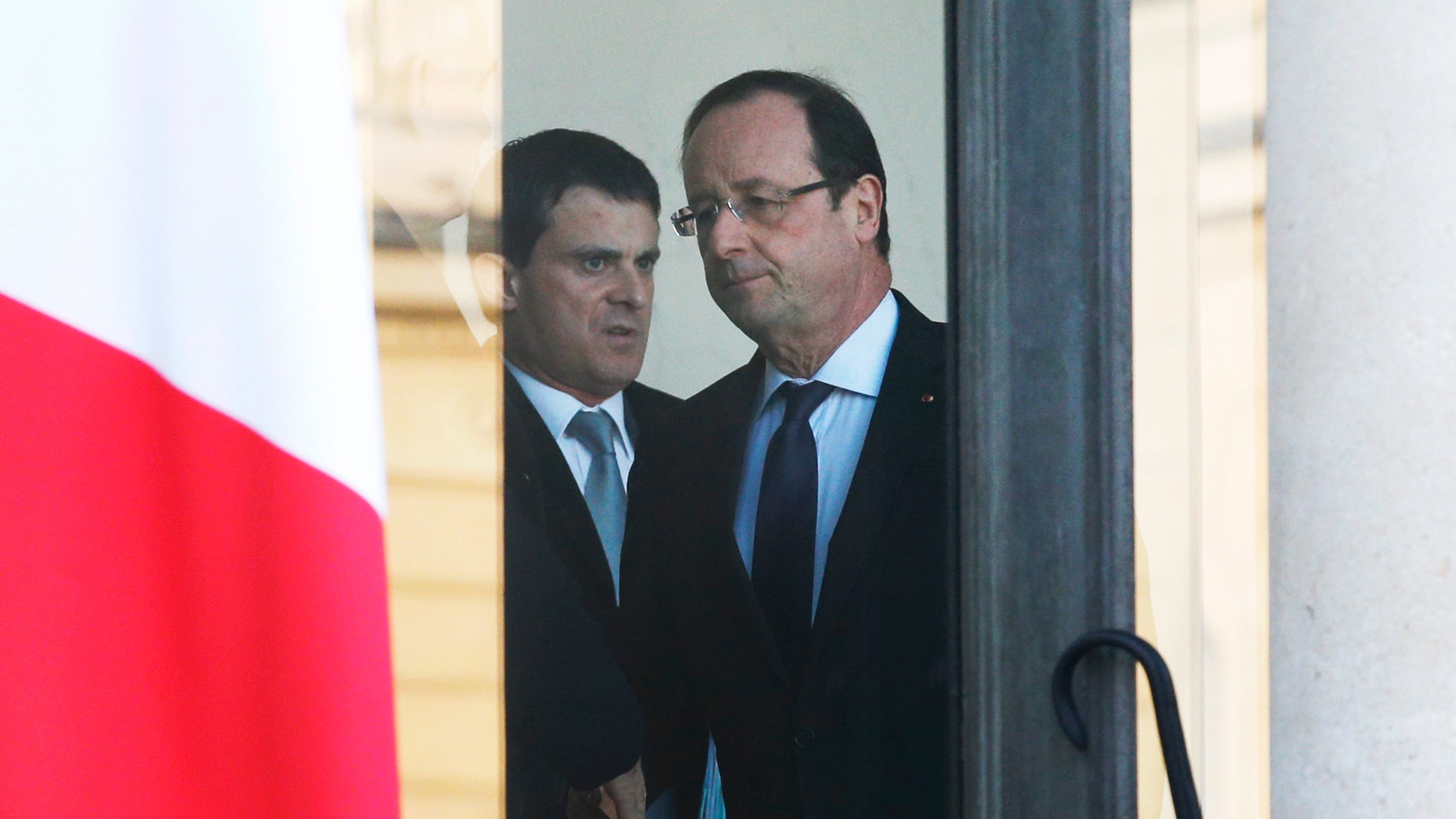 French President Francois Hollande, center right, and Interior Minister Manuel Valls leave after a meeting focused on the Malian situation, at the Elysee Palace in Paris, Monday, Jan. 14, 2013. French fighter jets bombed rebel targets in a major city in Mali's north Sunday, pounding the airport as well as training camps, warehouses and buildings used by the al-Qaida-linked Islamists controlling the area, officials and residents said. (AP Photo/Christophe Ena)