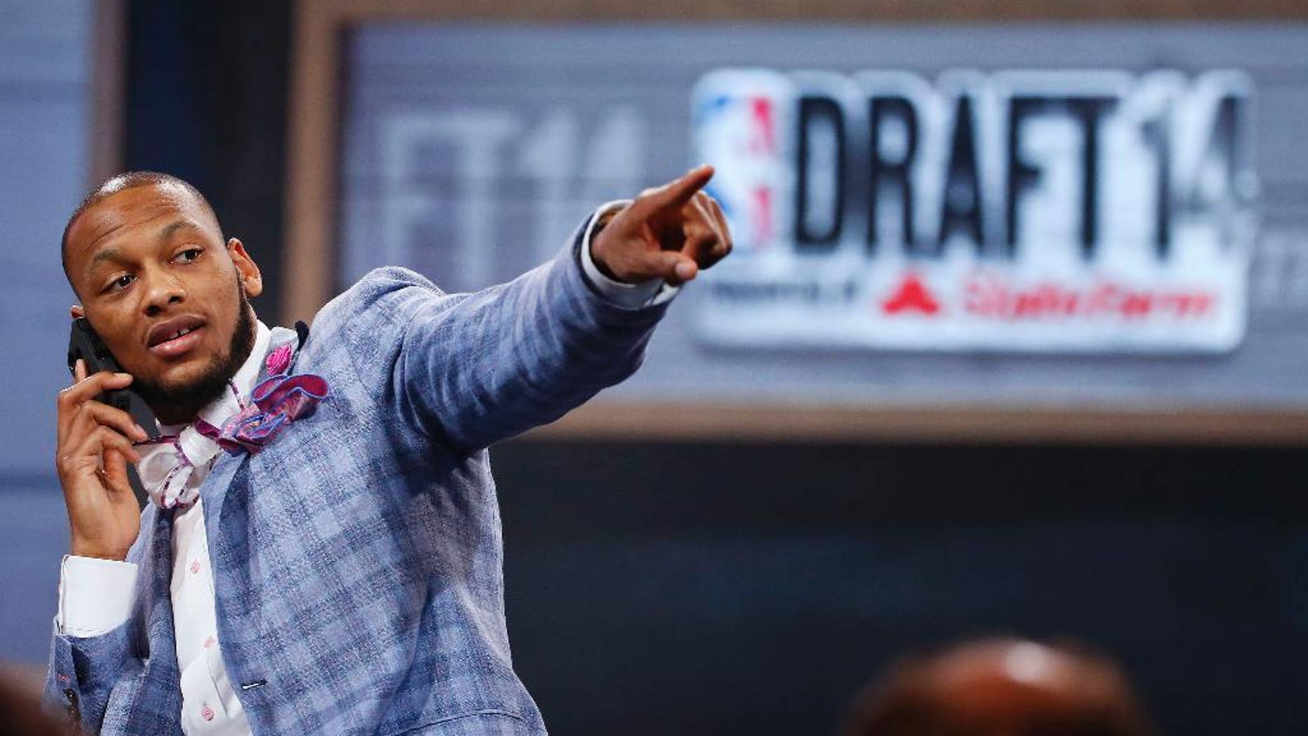 NBA draft prospect Adreian Payne of Michigan State, points to fans before the start of  the 2014 NBA draft, Thursday, June 26, 2014, in New York. (AP Photo/Jason DeCrow)