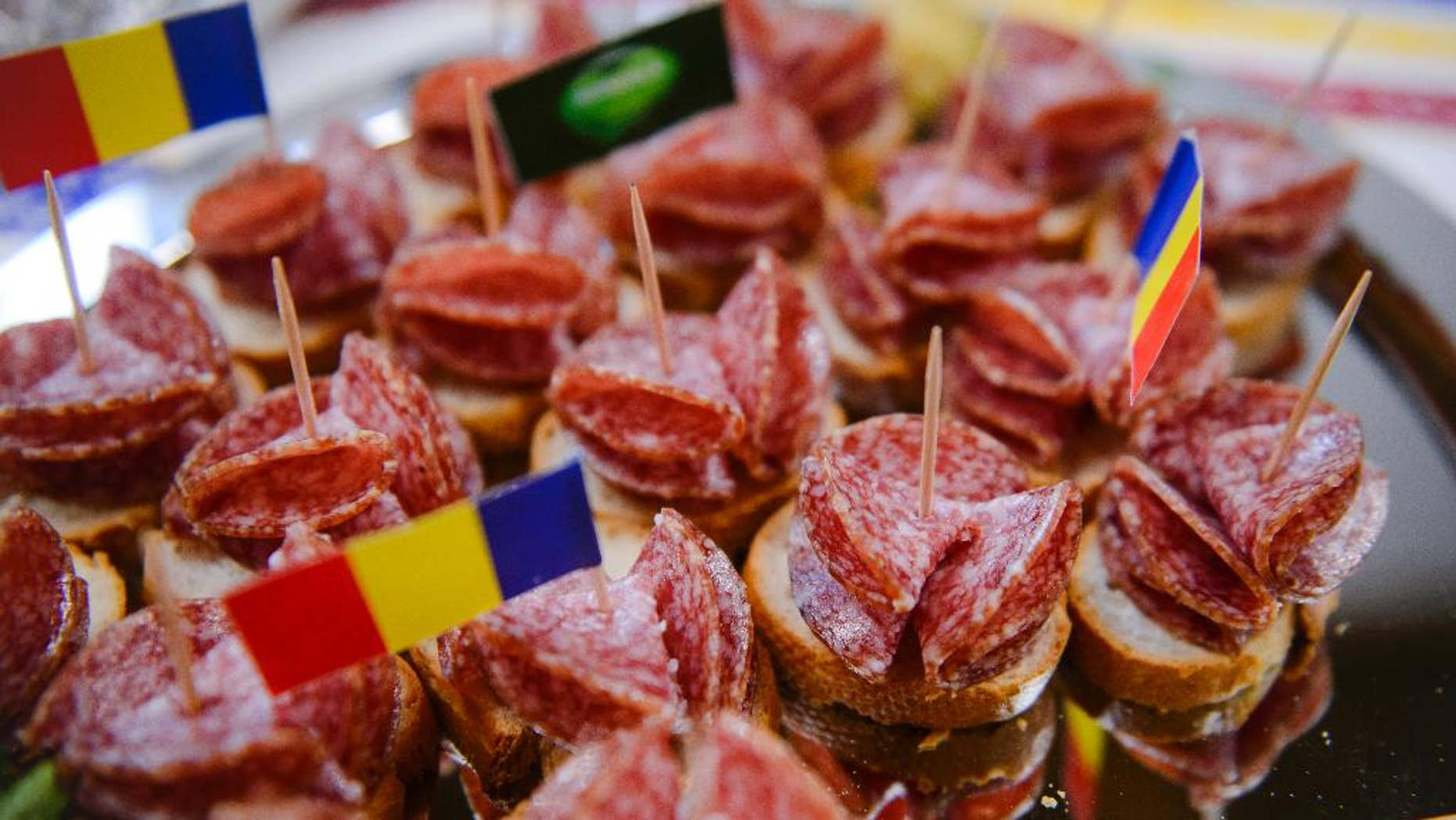 FILE- In this Friday, March. 18, 2016 file picture a platter of Sibiu salami, the local king of the smoked sausages, is presented to the media during a press conference, in Bucharest, Romania. Romanian lawmakers have adopted, Wednesday, June 8, 2016, legislation obliging supermarkets to sell at least 51 percent home-produced meat, fruit, eggs and vegetables in a move to support farmers.(AP Photo/Andreea Alexandru, File) ROMANIA OUT
