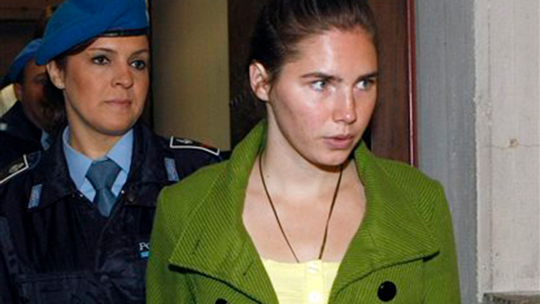 Dec. 4: Amanda Knox is accompanied by a penitentiary police officer prior to a final hearing at the court in Perugia, Italy. Knox was found guilty of murdering her British roommate Meredith Kercher. (AP photo)
