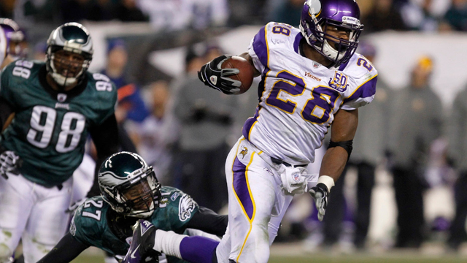 Minnesota Vikings running back Adrian Peterson (28) breaks a tackle from the Philadelphia Eagles safety Quintin Mikell (27) during the third quarter of their NFL football game in Philadelphia, Pennsylvania, December 28, 2010. REUTERS/Tim Shaffer (UNITED STATES - Tags: SPORT FOOTBALL)