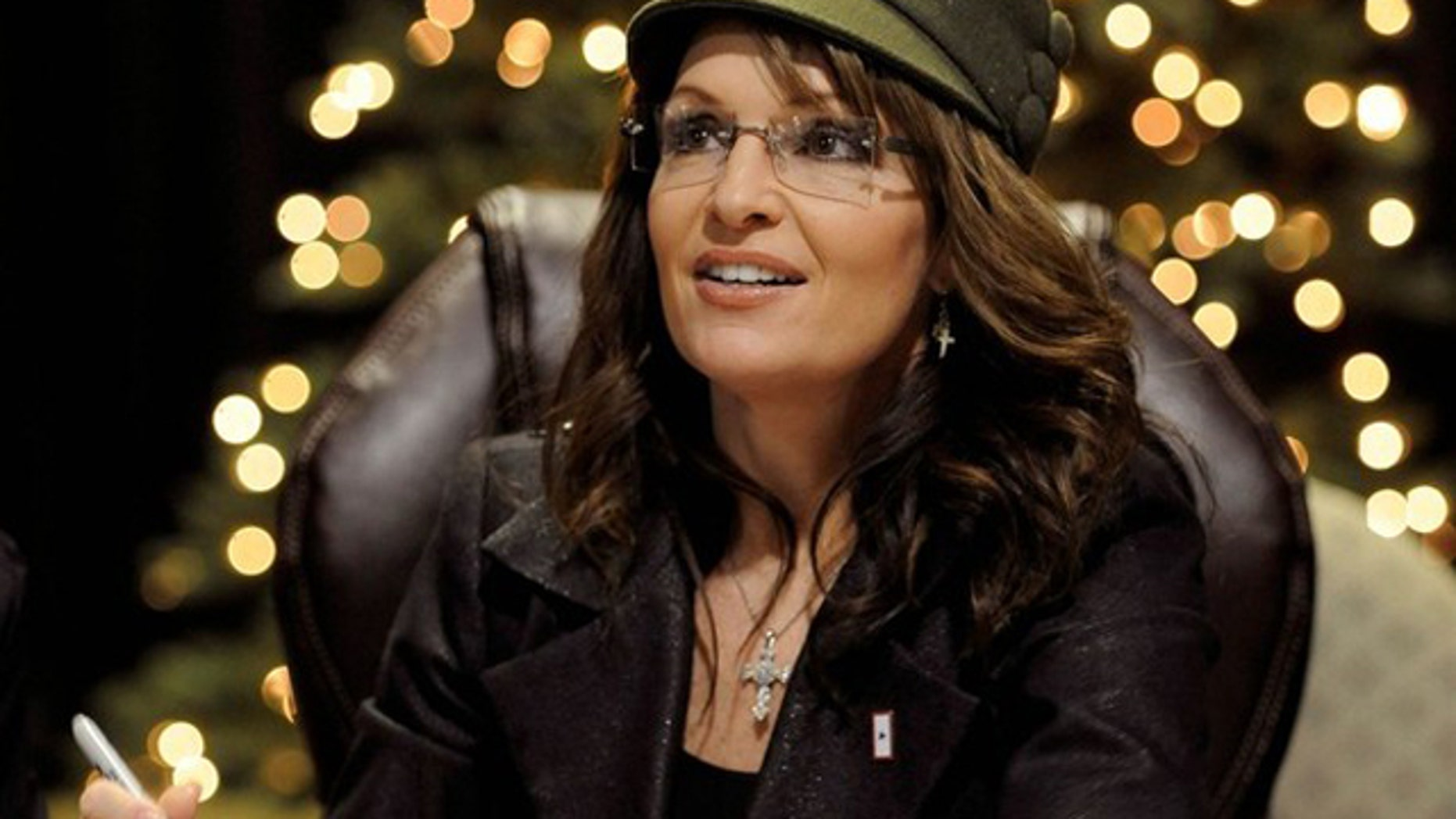 """Saturday: Former Alaska governor and 2008 Republican vice presidential nominee Sarah Palin signs her book """"Going Rogue"""" in front of a lit-up Christmas tree, at a shopping mall in Fairfax, Va.  (Reuters)"""