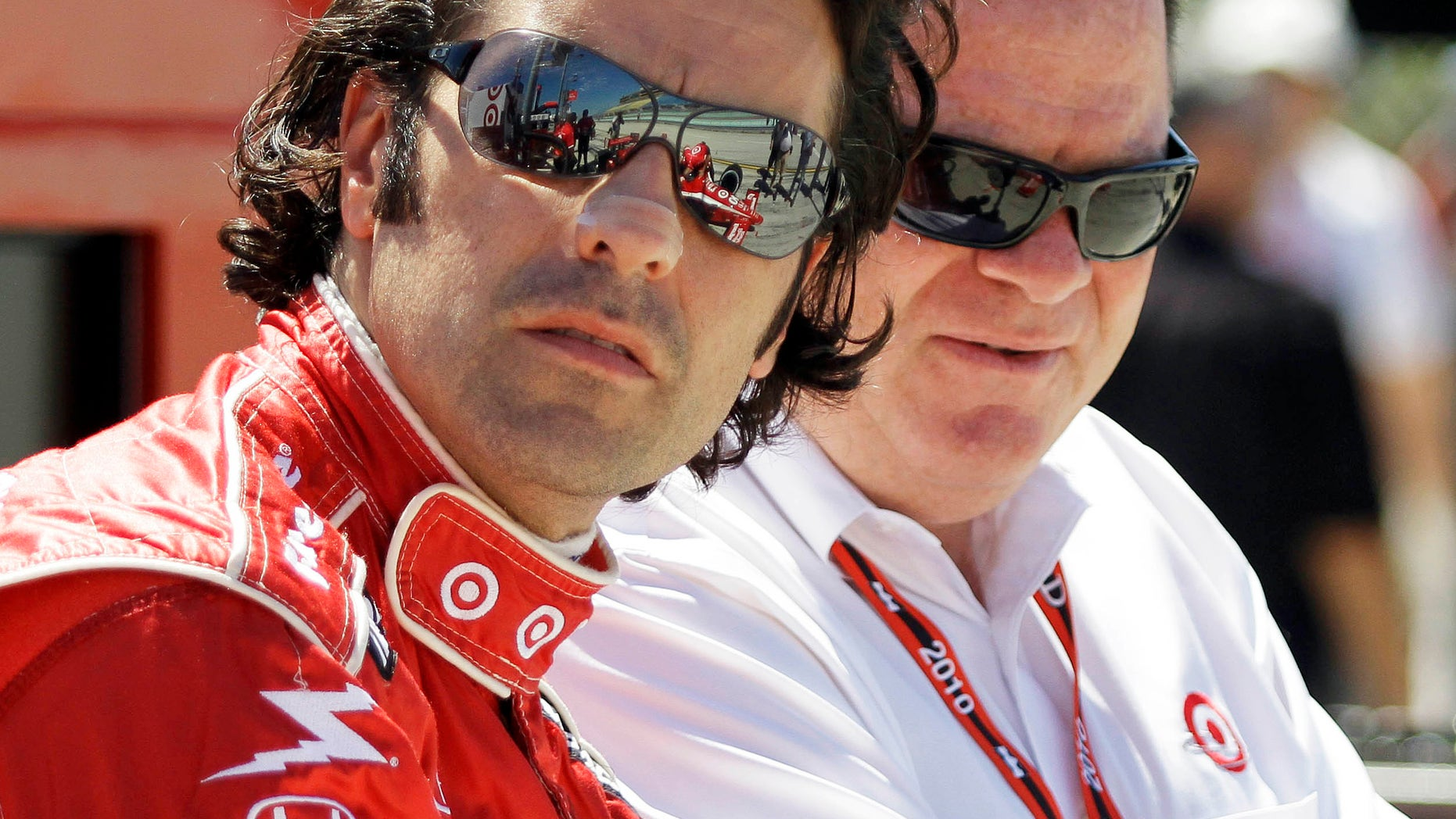 FILE - In this Oct. 1, 2010, file photo, IndyCar driver Dario Franchitti, left and team owner Chip Ganassi talk before practice for the IRL Indy 300 auto race at Homestead-Miami Speedway in Homestead, Fla. When Franchitti made a rare call from Scotland to his boss, Chip Ganassi knew immediately something was wrong. He could hear the heartbreak over the line. Franchitti then delivered the news: Doctors had told him it was time to quit.  (AP Photo/Terry Renna, File)