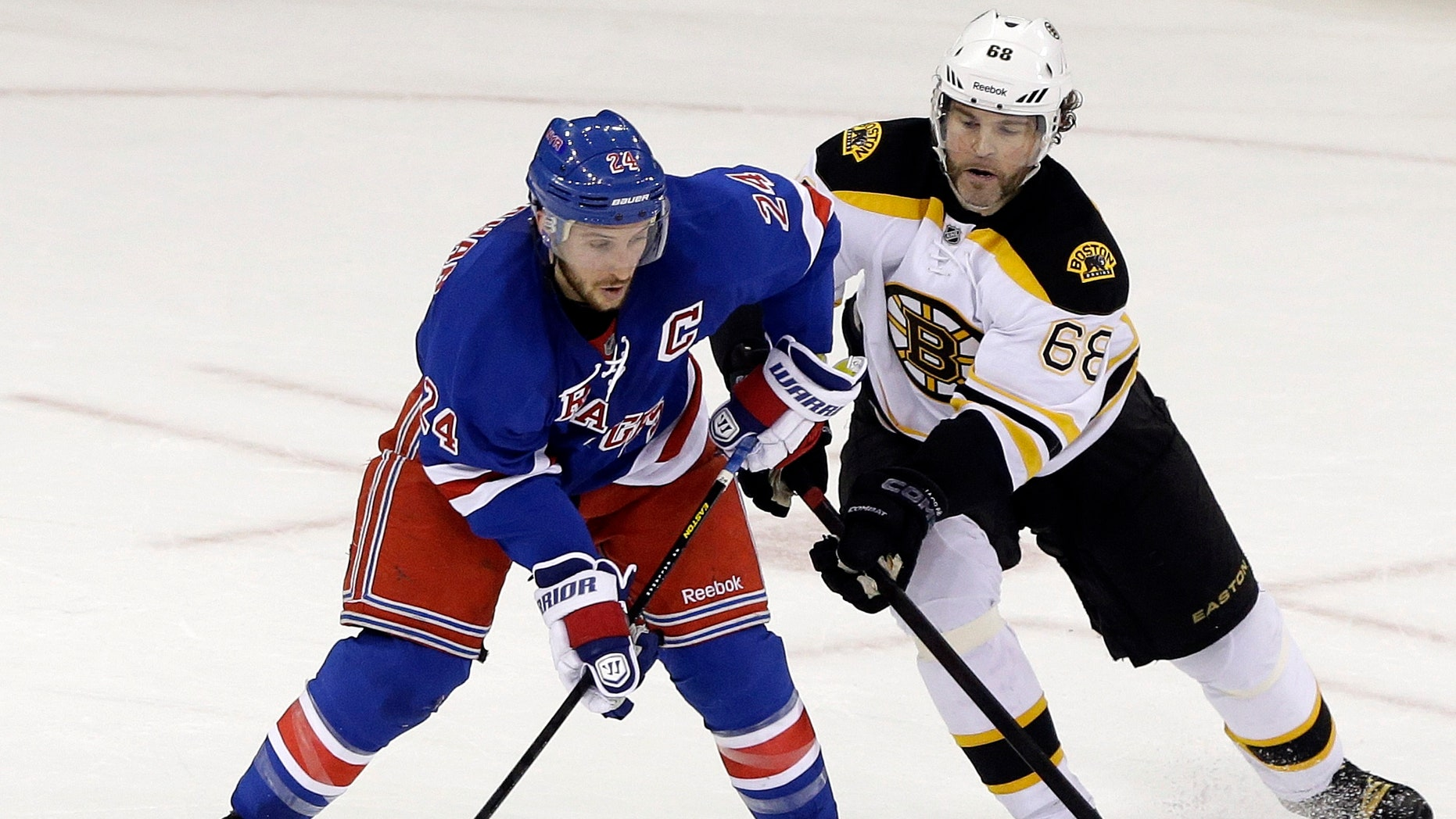 Boston Bruins' Jaromir Jagr (68) and Ryan Callahan (24) fight for control of the puck during the first period in Game 4 of the Eastern Conference semifinals in the NHL hockey Stanley Cup playoffs on Thursday, May 23, 2013, in New York. (AP Photo/Frank Franklin II)