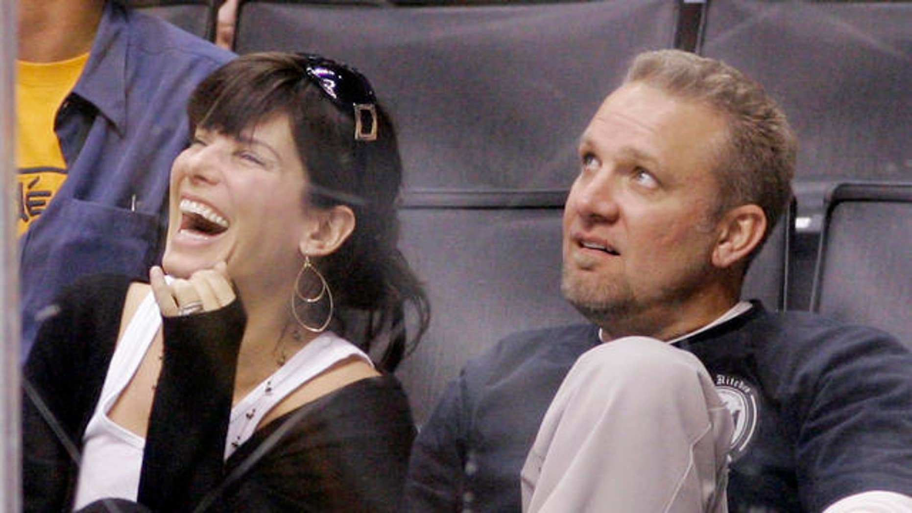 "**FILE** Actress Sandra Bullock laughs as she watches the video board with her husband Jesse James during the Los Angeles Kings' NHL hockey game against the Anaheim Ducks, in this Oct. 22, 2006 file photo in Los Angeles. Before she got to know him, Bullock says she tagged her husband as a brutish ""bigot."" (AP Photo/Mark J. Terrill, file)"