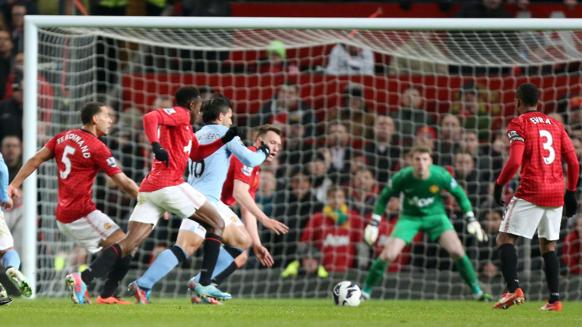 Sergio Agüero, en azul, se abre paso para anotar un gol para el Manchester City ante Manchester United el lunes 8 de abril de 2013. (AP Foto/Jon Super)