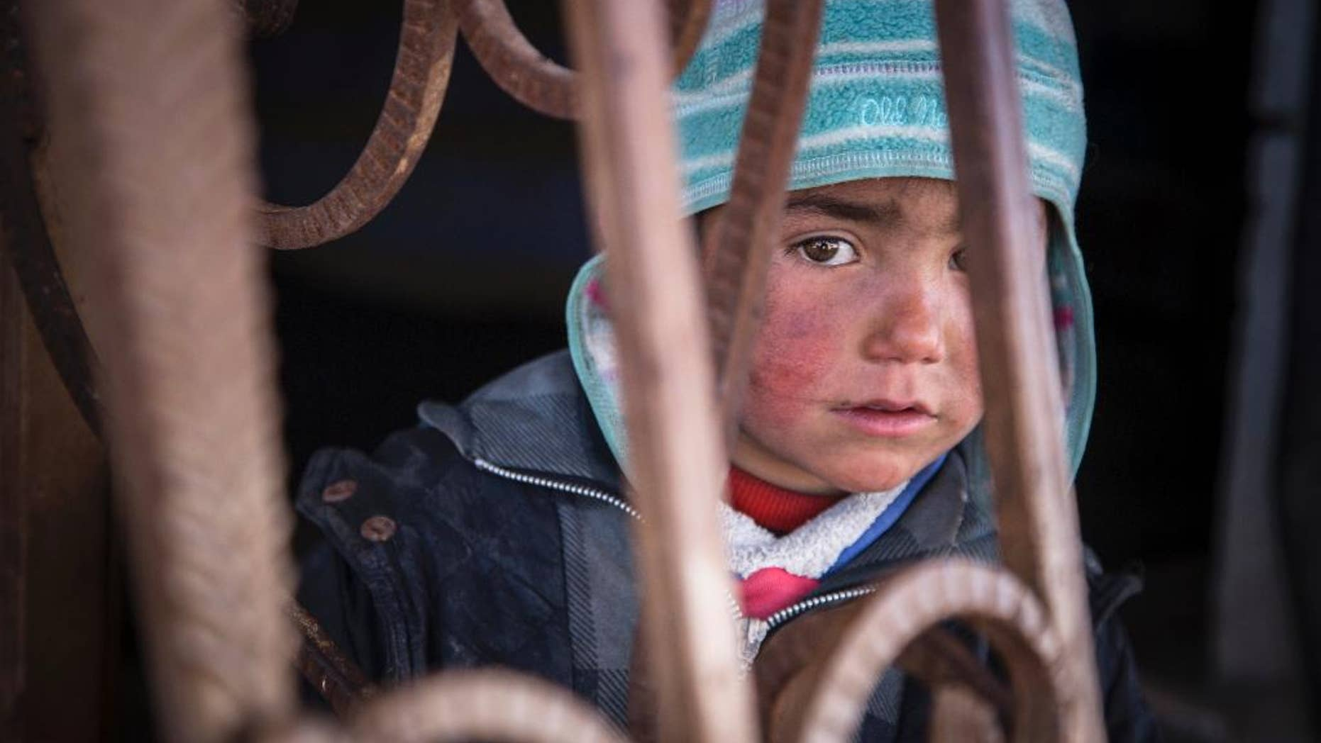 In this picture taken, Feb. 16, 2017, a child looks out from an abandoned petrol station where he and his family now live. The petrol station, badly damaged by war, is now the home of five families who have returned to Tel Abiad district, Raqqa Governorate, Syria, after fleeing from ISIS two years earlier only to find their homes destroyed. A new report by Save the Children says Syrian children are showing symptoms of 'toxic stress' from war exposure, and attempting self-harm and suicide. (Photo Courtesy: Jonathan Hyams, Save the Children via AP)