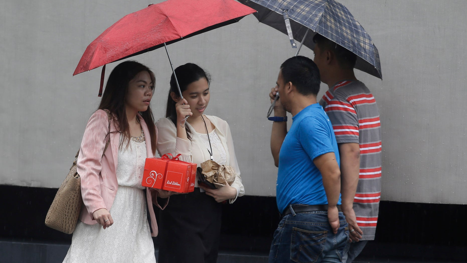 Filipinos use umbrellas as they go on their daily business at the financial district of Makati city east of Manila, Philippines under a slight rain Friday Oct. 11, 2013. A tropical storm barreling toward the northern Philippines on Friday intensified into a typhoon with destructive winds and flooding rains threatening farmlands and populated areas, including the capital Manila. Typhoon Nari forced U.S. Secretary of State John Kerry to call off Friday's trip to the Philippines. (AP Photo/Bullit Marquez)