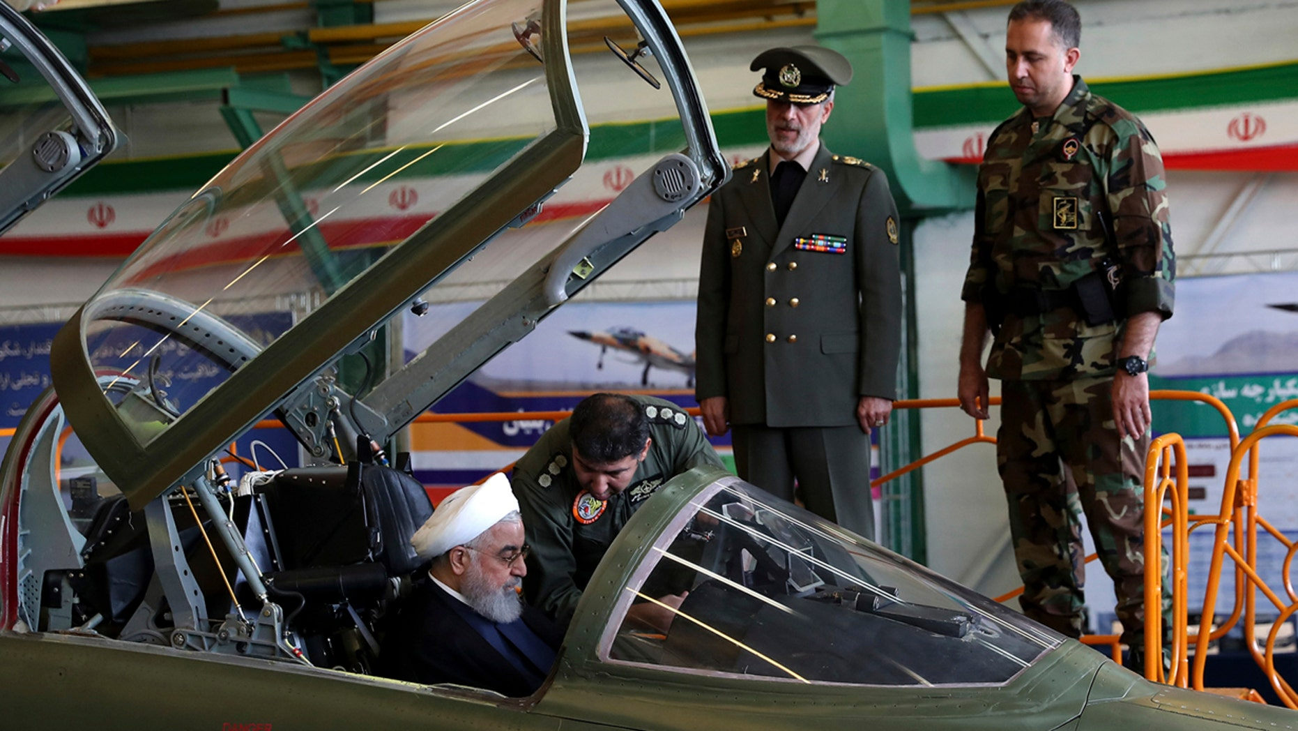 In this photo released by official website of the office of the Iranian Presidency, President Hassan Rouhani is briefed by an air force pilot as he sits in the cockpit of a fighter jet, before an inauguration ceremony of the aircraft, Iran.