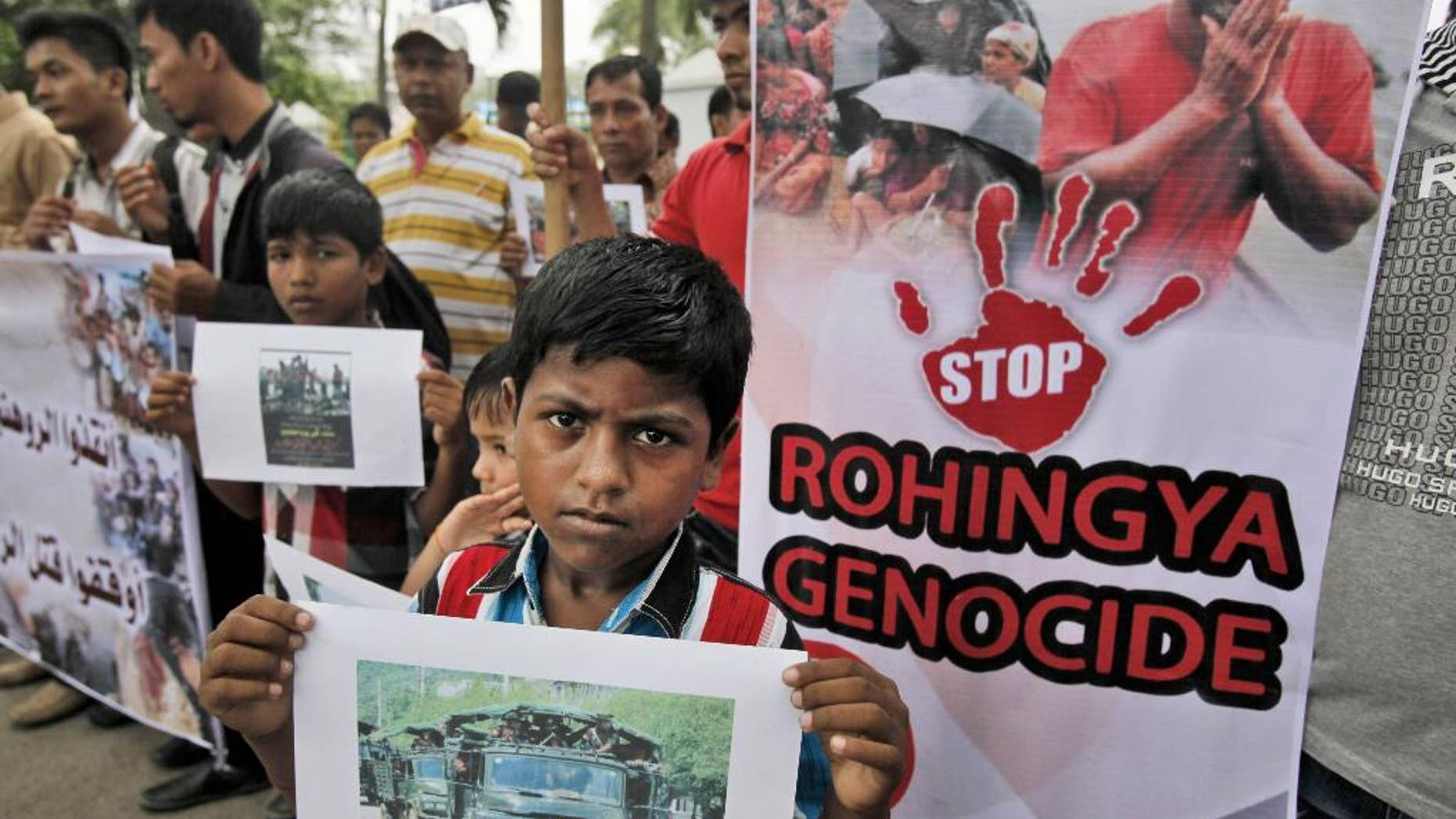 Ethnic Rohingya migrants hold banners during a rally in Medan, North Sumatra, Indonesia, Tuesday, May 12, 2015. Hundreds of migrants abandoned at sea by smugglers in Southeast Asia have reached land and relative safety in the past two days. But an estimated 6,000 Bangladeshis and Rohingya Muslims from Myanmar remain trapped in crowded, wooden boats, migrant officials and activists said. With food and clean water running low, some could be in grave danger. (AP Photo/Binsar Bakkara)