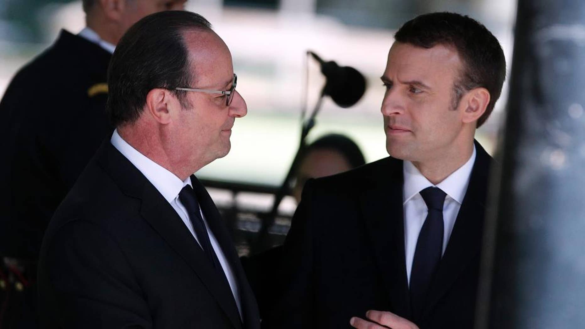 Outgoing French President Francois Hollande, left, and French President-elect Emmanuel Macron shake hands as they attend a ceremony commemorating the abolition of slavery, in Paris, Wednesday, May 10, 2017. (AP Photo/Christophe Ena)