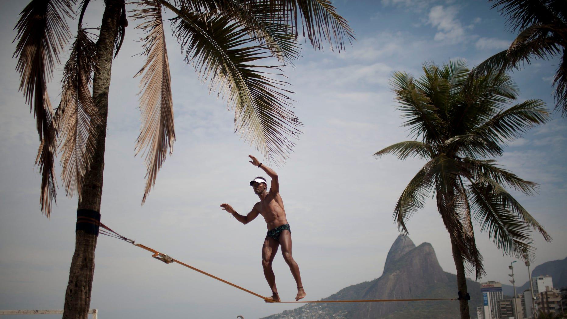 Waltinho da Silva, 48, practices slacklining at Ipanema Beach in Rio de Janeiro, Brazil, Saturday Aug. 20, 2011. (AP Photo/Felipe Dana)