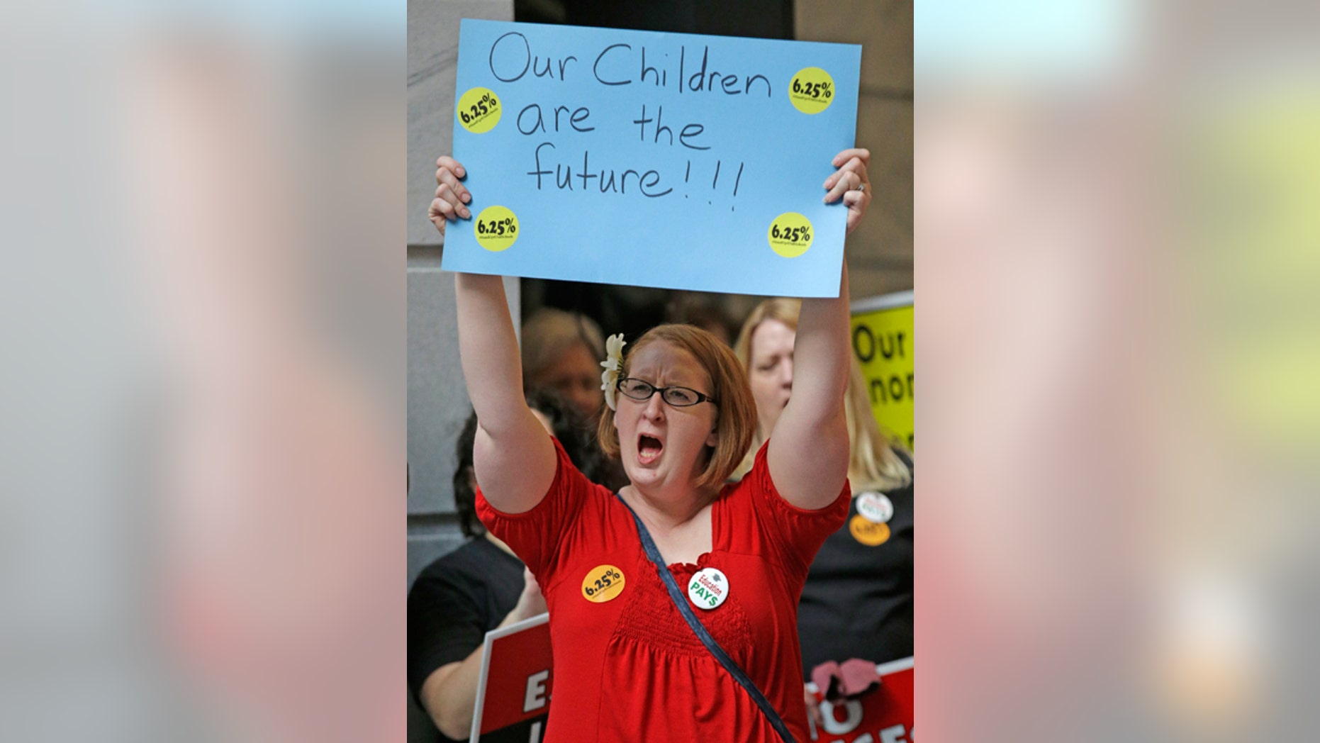 FILE -- March 9, 2015: Kristi Jacobsen, a second grade teacher from Ogden, shows her support while gathered with others during the stand up for public education rally at the Utah State Capitol Monday, , in Salt Lake City.