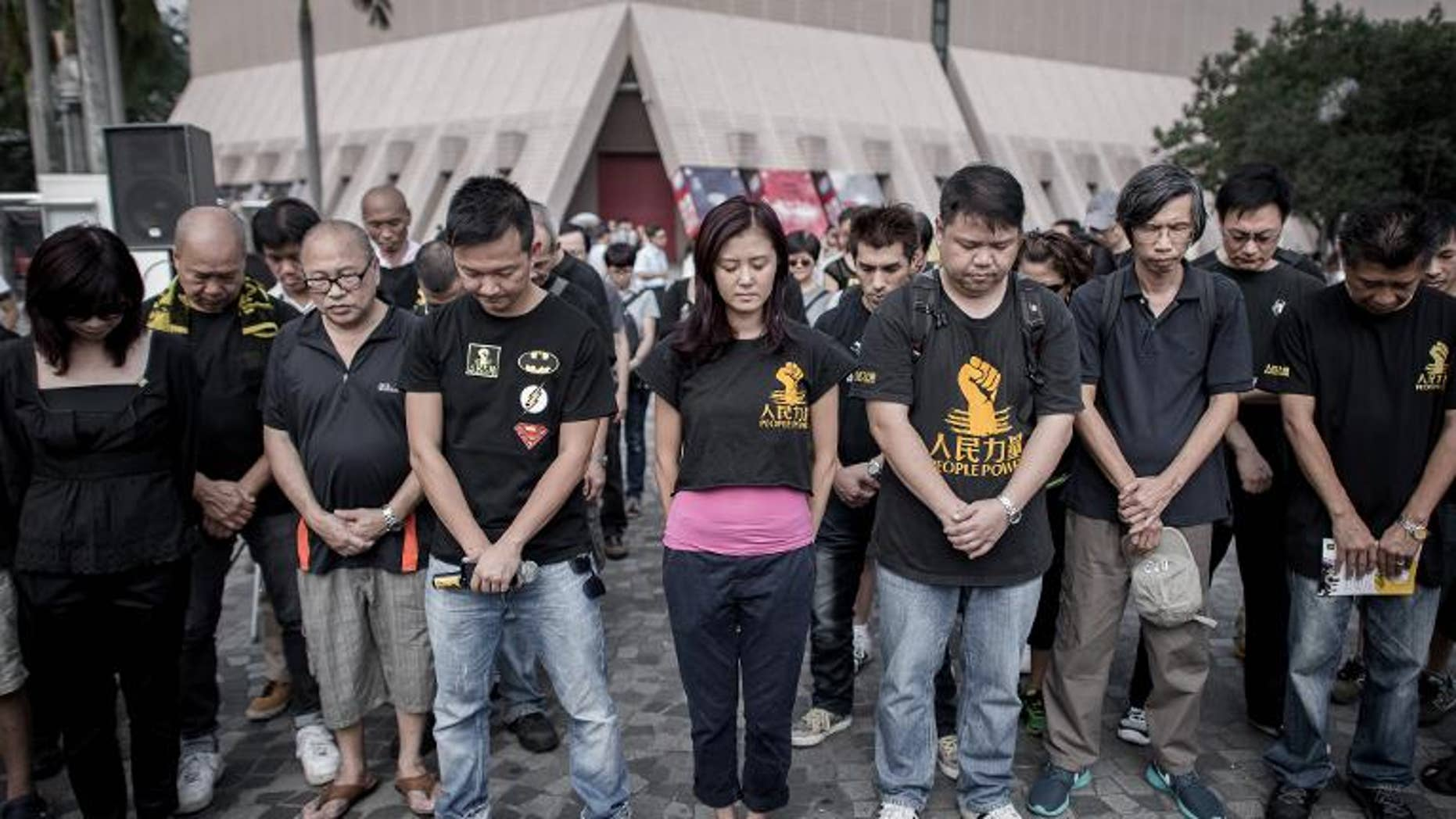 Around a dozen people wearing black clothes hold a minute's silence to mark the first anniversary of a fatal sea disaster which claimed 39 lives in Hong Kong on October 1, 2013
