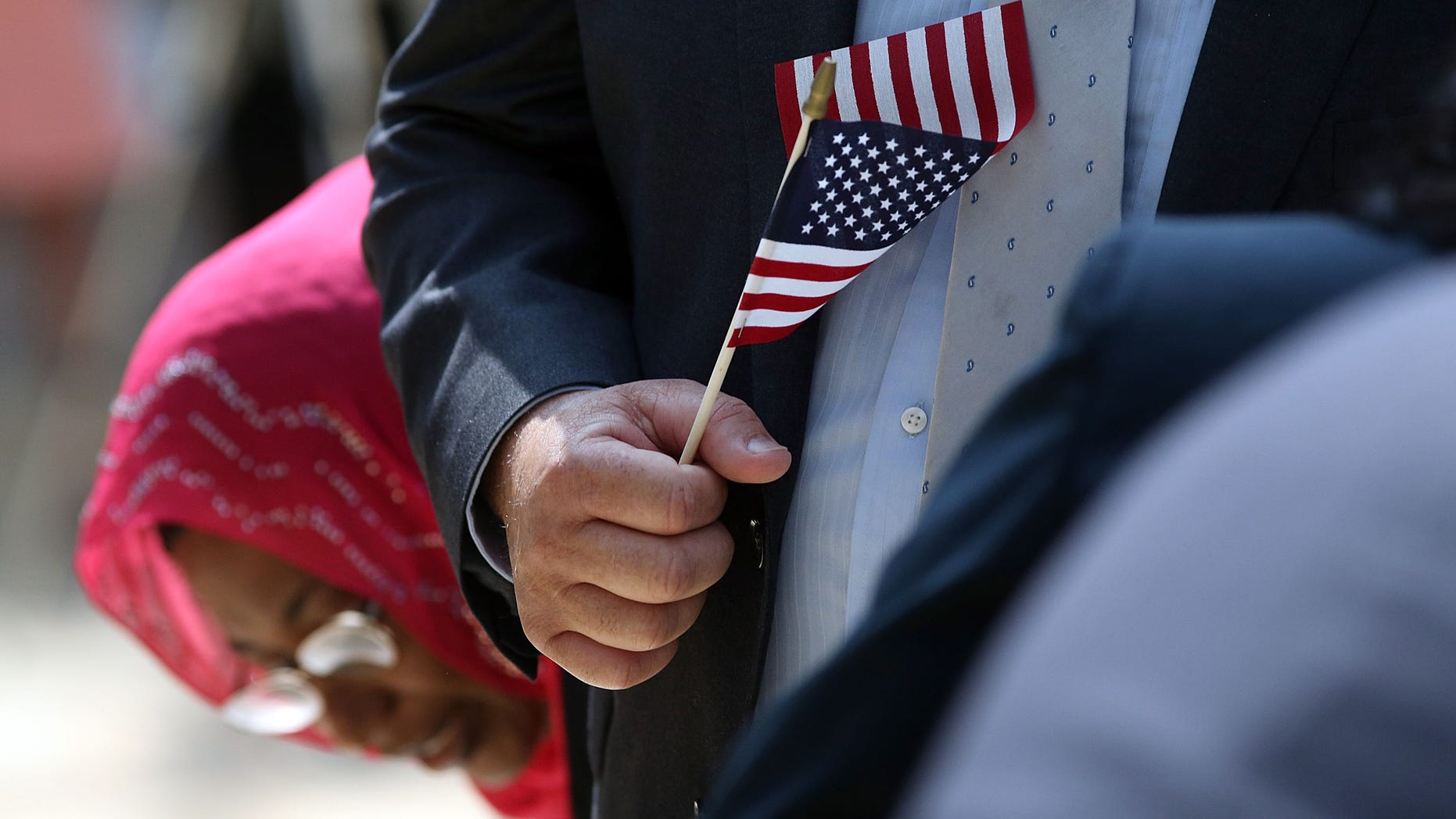 NEW YORK, NY - JULY 22: A man holds an American Flag before taking the Oath of Allegiance during a special naturalization ceremony at the Metropolitan Museum of Art on July 22, 2014 in New York City. Over fifty people representing countries from Albania to Burundi took part in the morning ceremony at the American Wing of the museum. The Oath of Allegiance was administered by U.S. Citizenship and Immigration Services (USCIS) Deputy Director Lori L. Scialabba. (Photo by Spencer Platt/Getty Images)