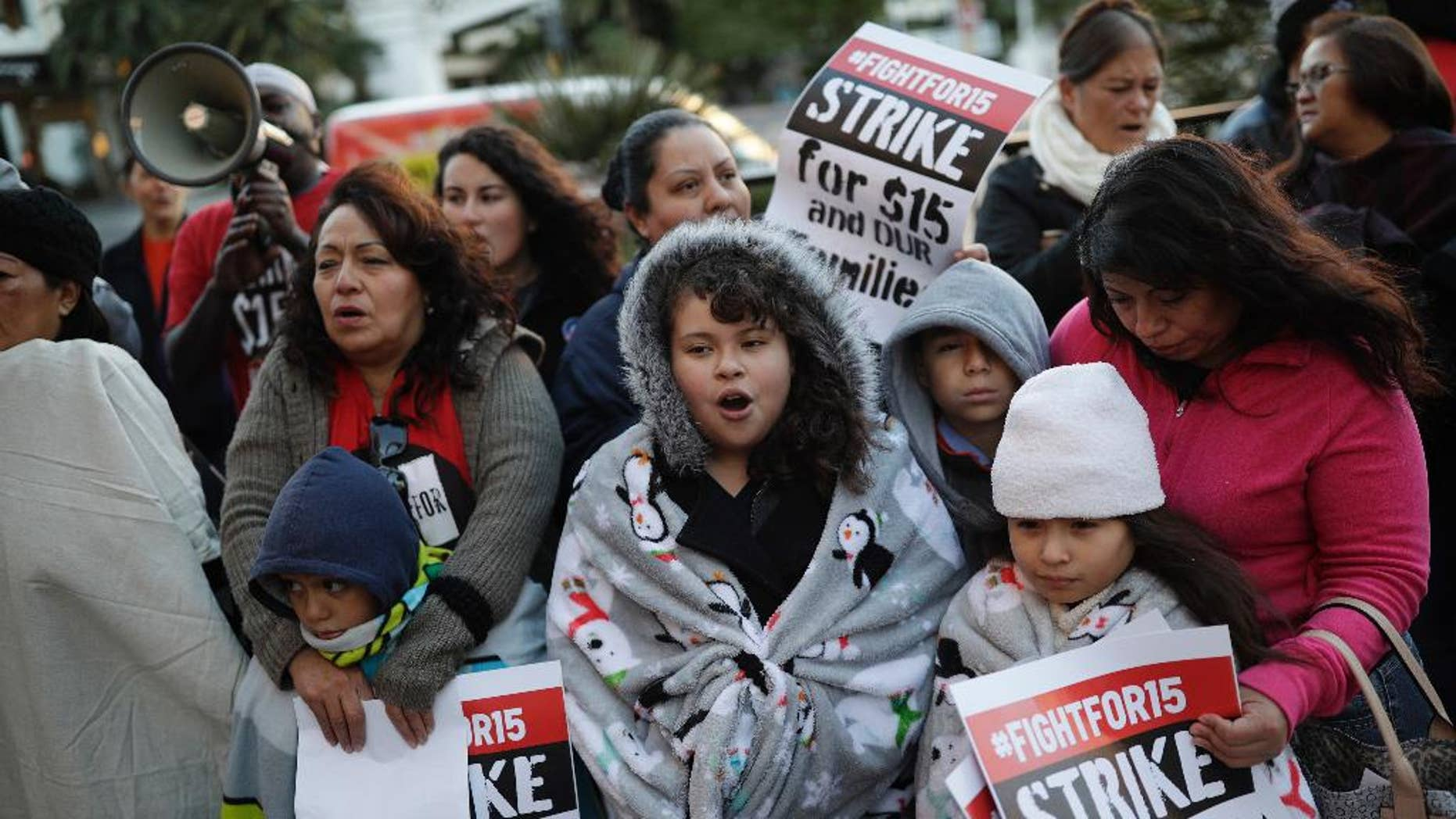 "FILE – In this Nov. 29, 2016, file photo, people protest as part of the National Day of Action to Fight for $15 near a McDonald's restaurant along the Las Vegas Strip in Las Vegas. A cluster of Black Lives Matter groups and the organization leading the push for a $15-an-hour wage are joining forces to combine the struggle for racial justice with the fight for economic equality, just as the Rev. Martin Luther King Jr. tried to do in the last year of his life. They are launching their first national joint action on April 4, 2017, the 49th anniversary of King's assassination, with ""Fight Racism, Raise Pay"" protests in two dozen cities, including Atlanta; Chicago; Boston; Denver; and Las Vegas. (AP Photo/John Locher, File)"