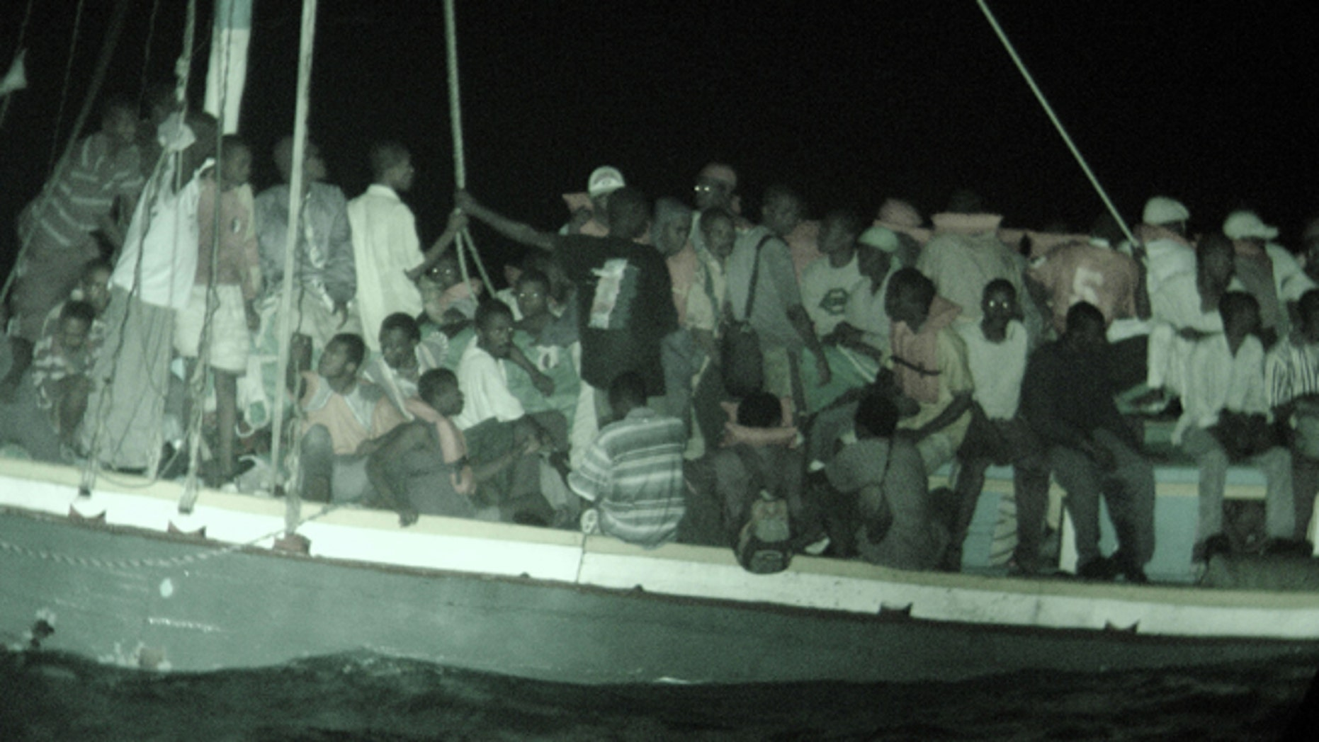 AT SEA - APRIL 30:  In this handout photo provided by the U.S. Coast Guard, Haitian migrants wait aboard a 50-foot sailboat to be brought by small boat to the Coast Guard cutter Dependable April 30, 2005 in the Windward Pass, northwest of Haiti. The crew of the Dependable rescued 132 migrants from Haiti from the overloaded 50-foot sail freighter, who were later safely repatriated.  (Photo by U.S. Coast Guard via Getty Images)